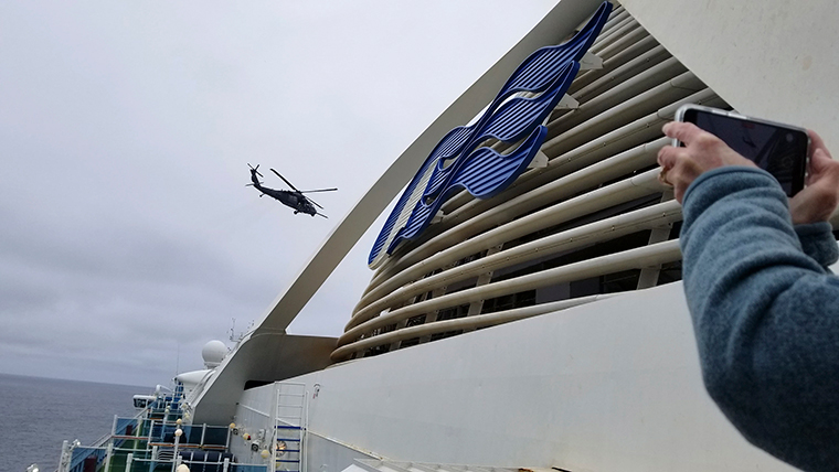 In this photo provided by Michele Smith, a Coast Guard helicopter delivering virus testing kits hovers above the Grand Princess cruise ship Thursday, March 5, off the California coast.