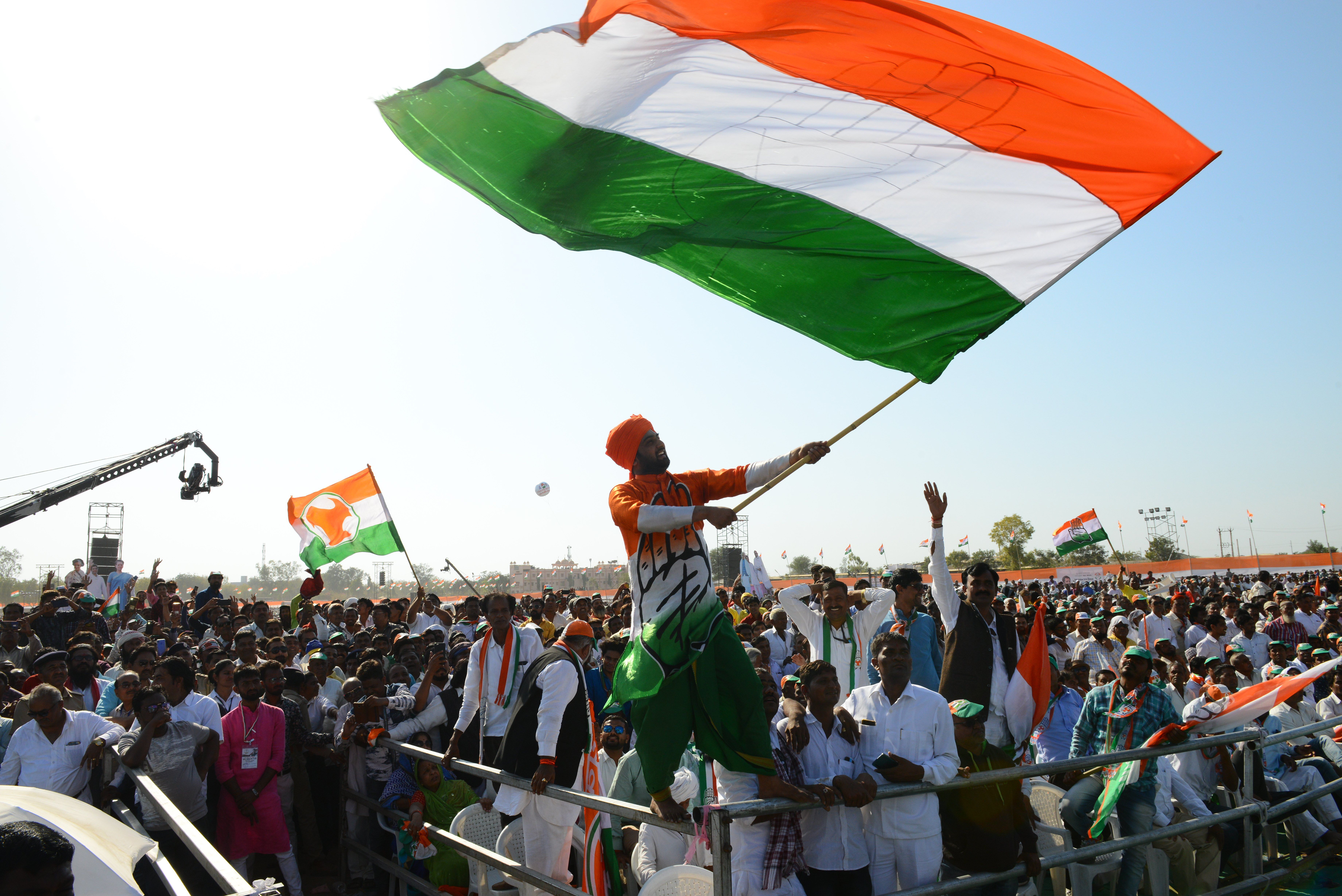 Supporters of the Congress party wave flags as party president Rahul Gandhi speaks during a rally on March 12, 2019.