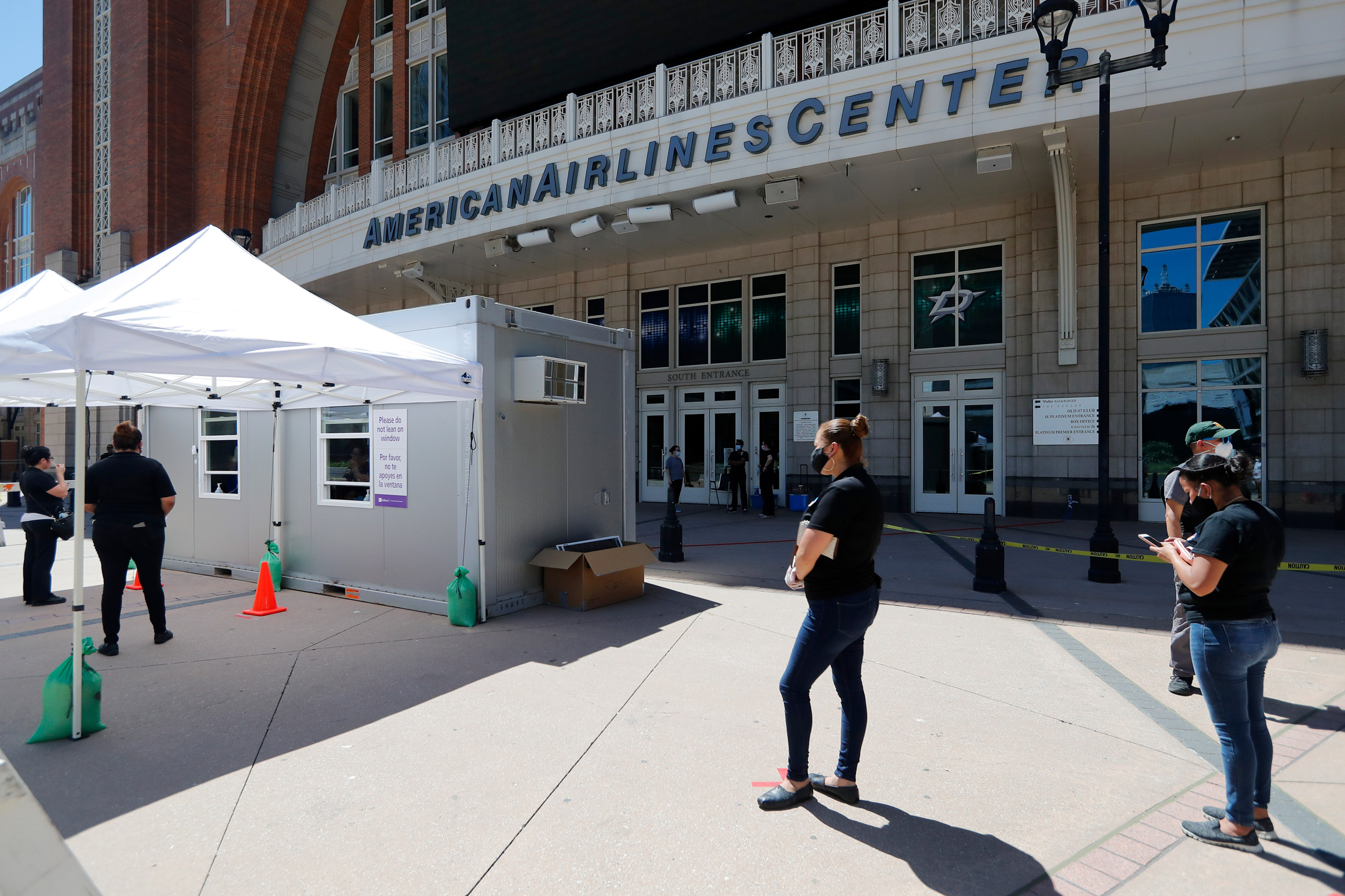 Persons  wait in line at a walk up COVID-19 test site in front of American Airlines Center in Dallas on June 11.