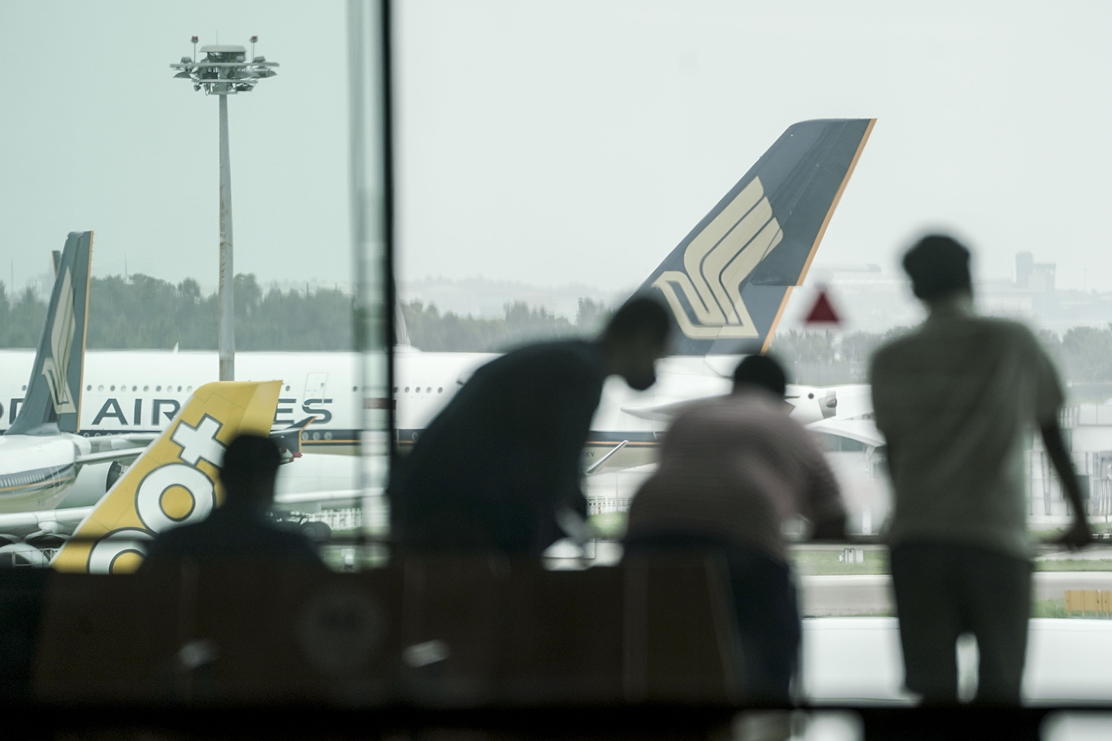 Three men wait to board a plan at the Changi Airport in Singapore on January 13.