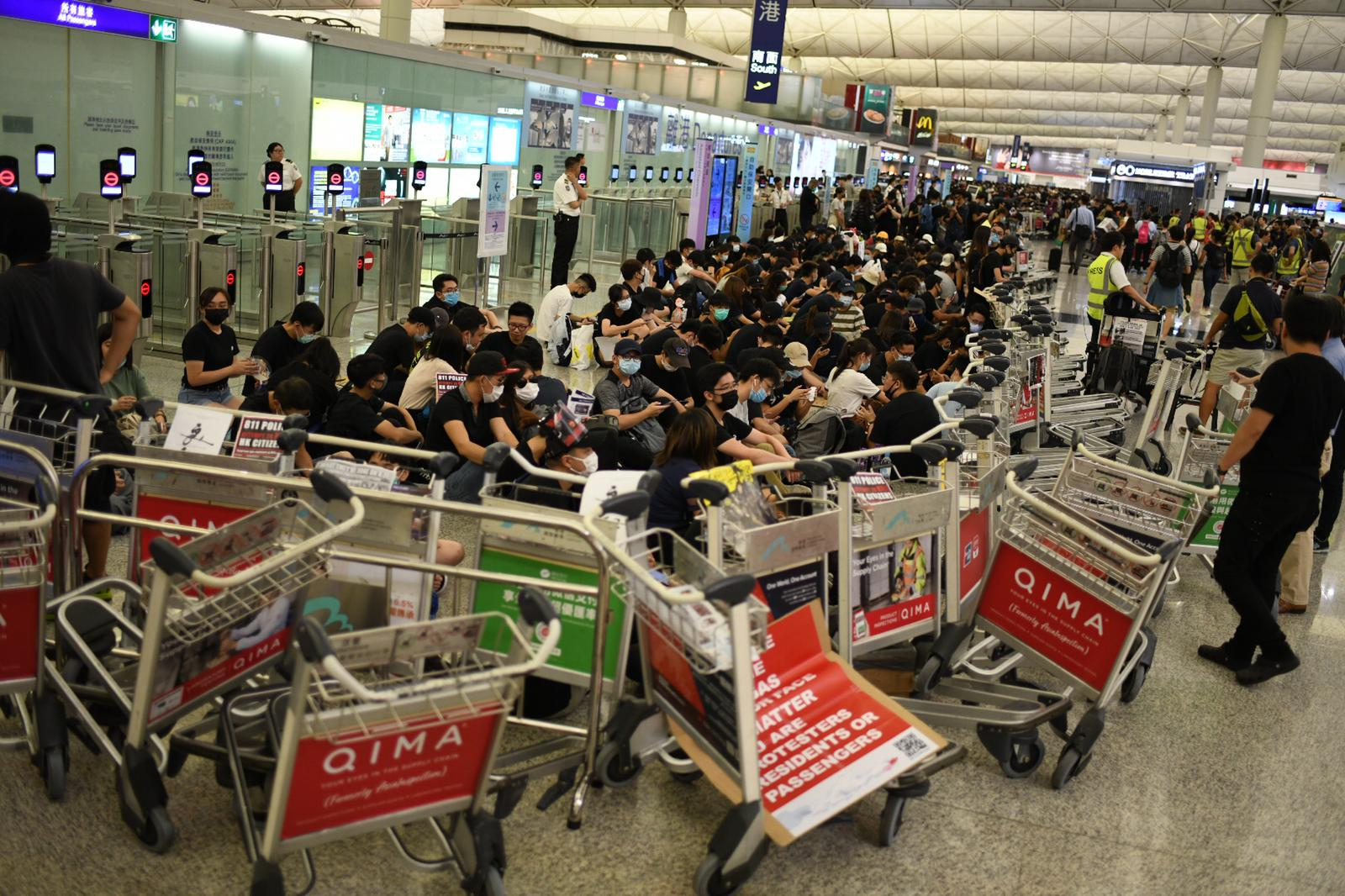Protesters build a blockade of luggage carts around the entrance to the security area at Hong Kong airport.