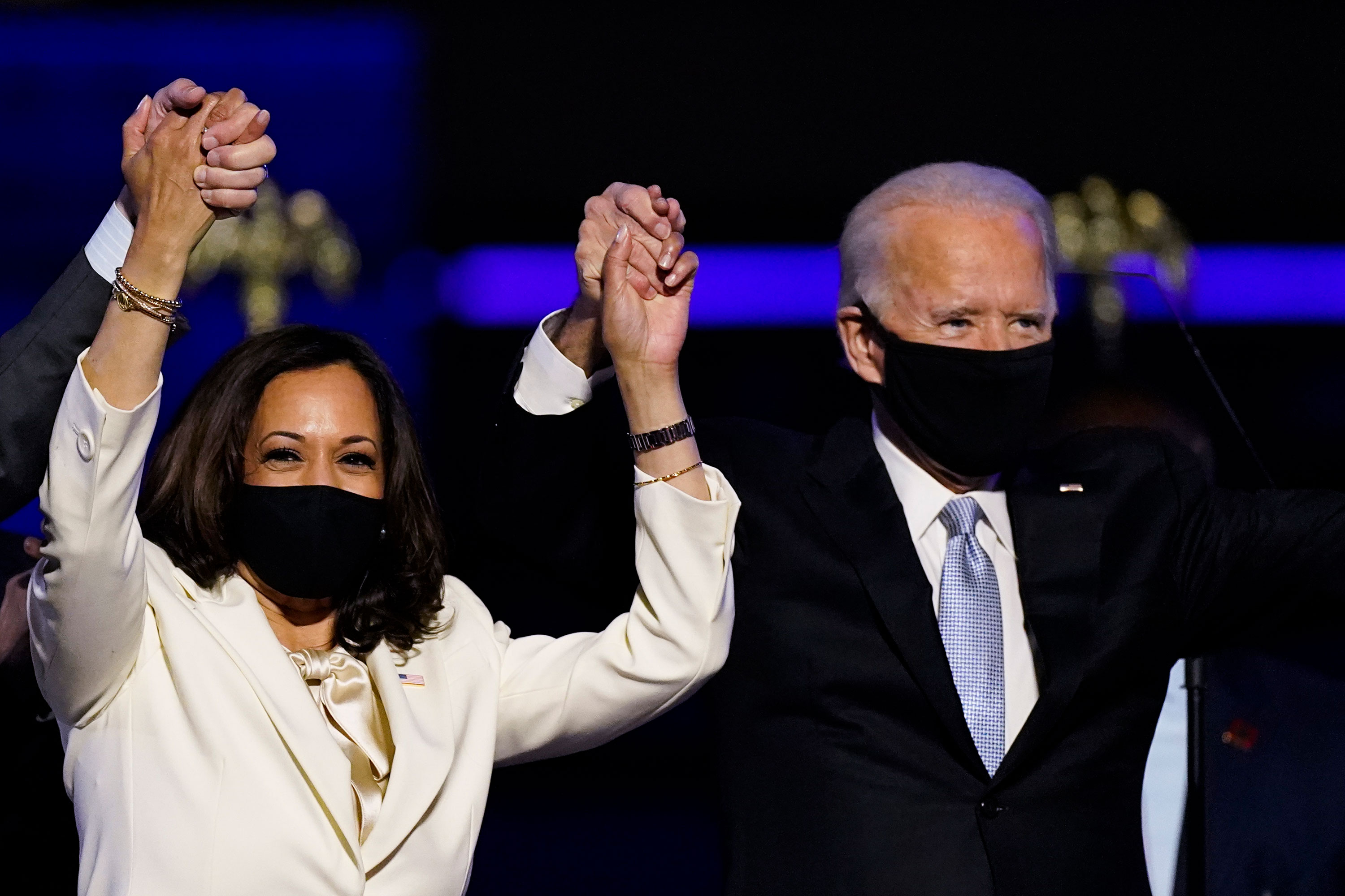 Vice President-elect Kamala Harris holds hands with President-elect Joe Biden and her husband Doug Emhoff as they celebrate Saturday, Nov. 7, 2020, in Wilmington, Del