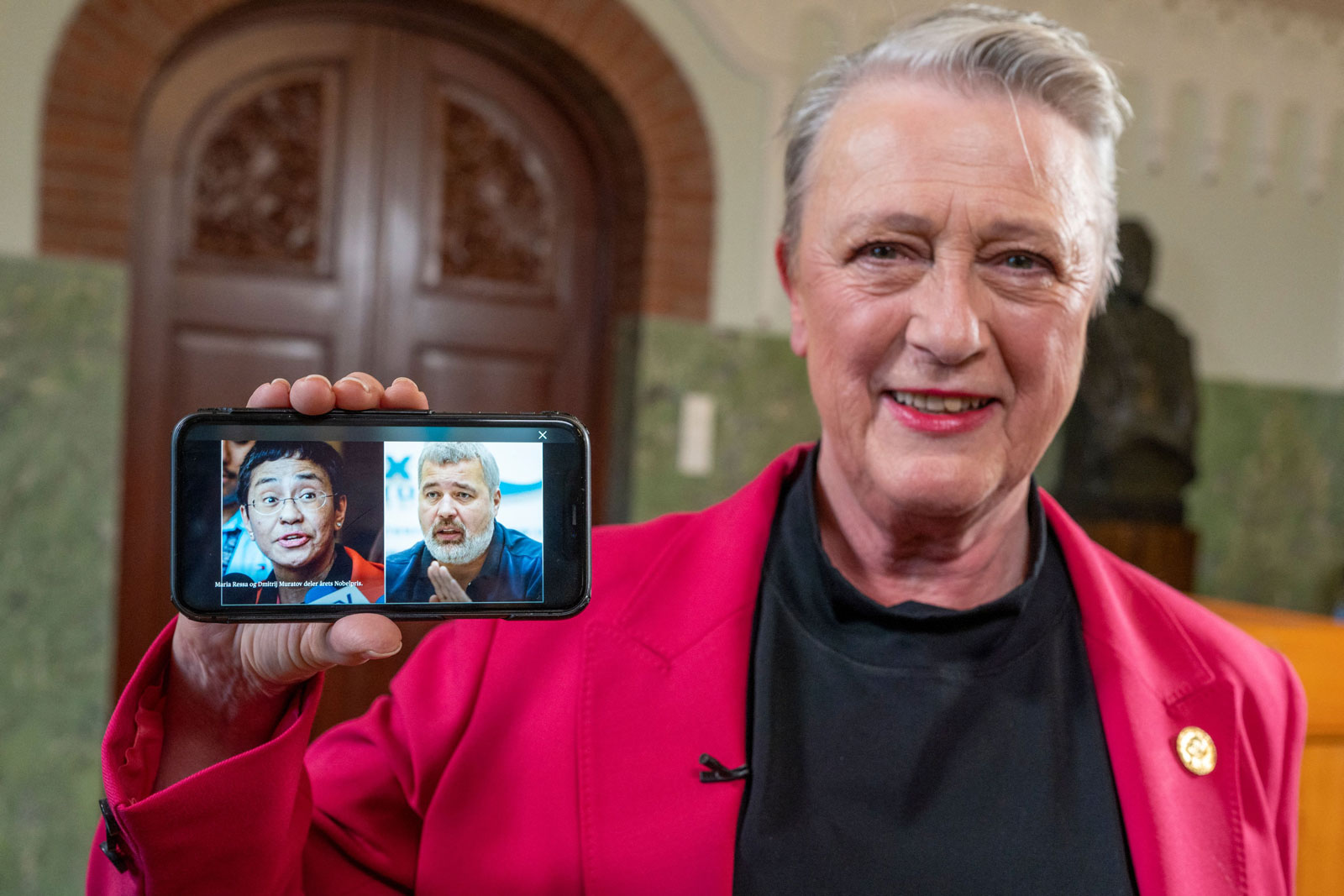 Berit Reiss-Andersen, chair of the Nobel Peace Prize Committee, presents a mobile phone displaying photos of journalists Maria Ressa and Dmitry Muratov following a press conference to announce the winners of the 2021 Nobel Peace Prize.