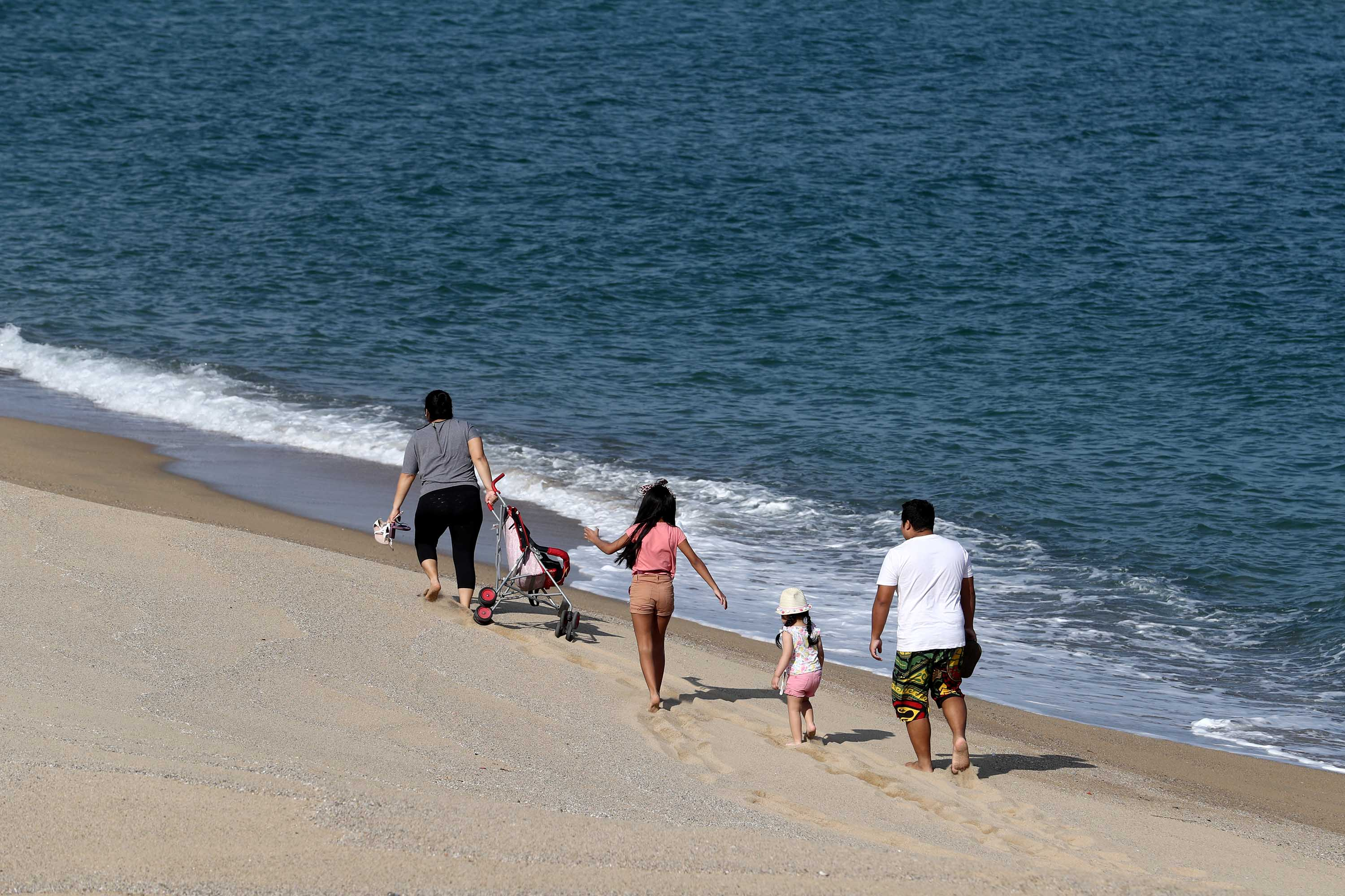 A family walks on a beach in Barcelona, Spain, on April 26, after some lockdown restrictions were lifted.