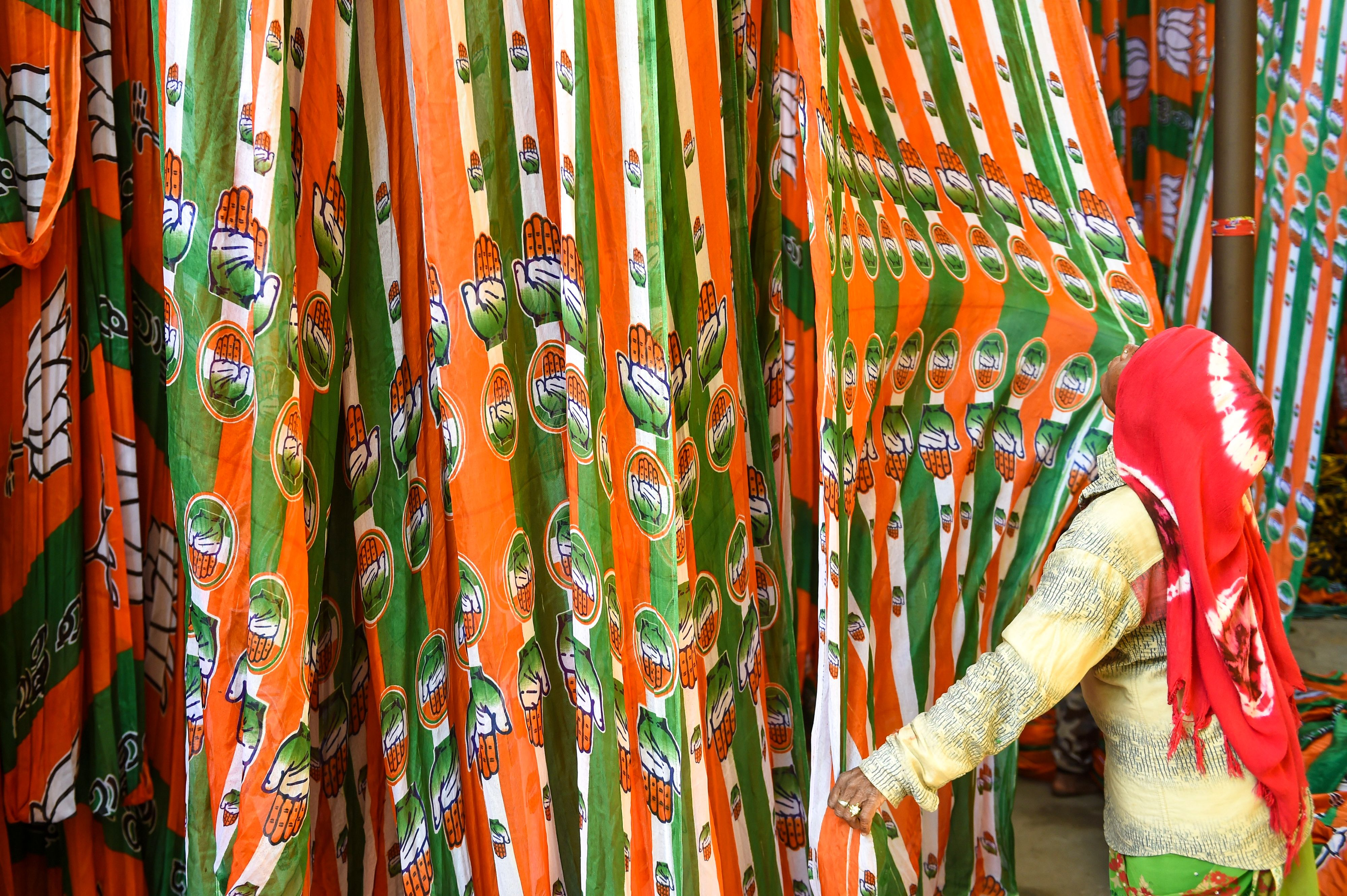 A worker dries materials bearing the colors of India's opposition Congress Party on March 11.