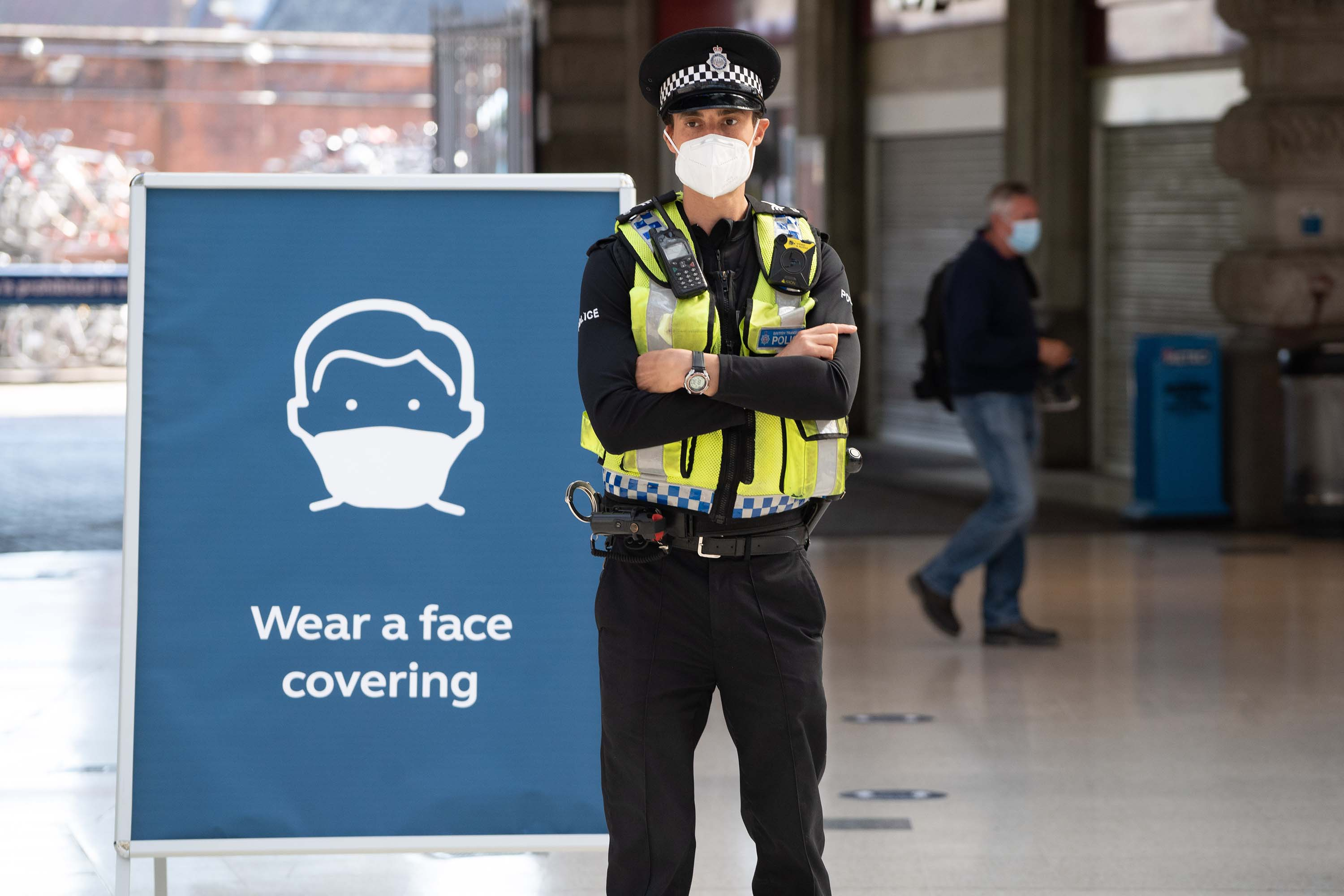 A police officer wears a face mask as he stands on the concourse at Waterloo Station in London on Monday, June 15, after new rules came into effect, making wearing face coverings on public transport compulsory.