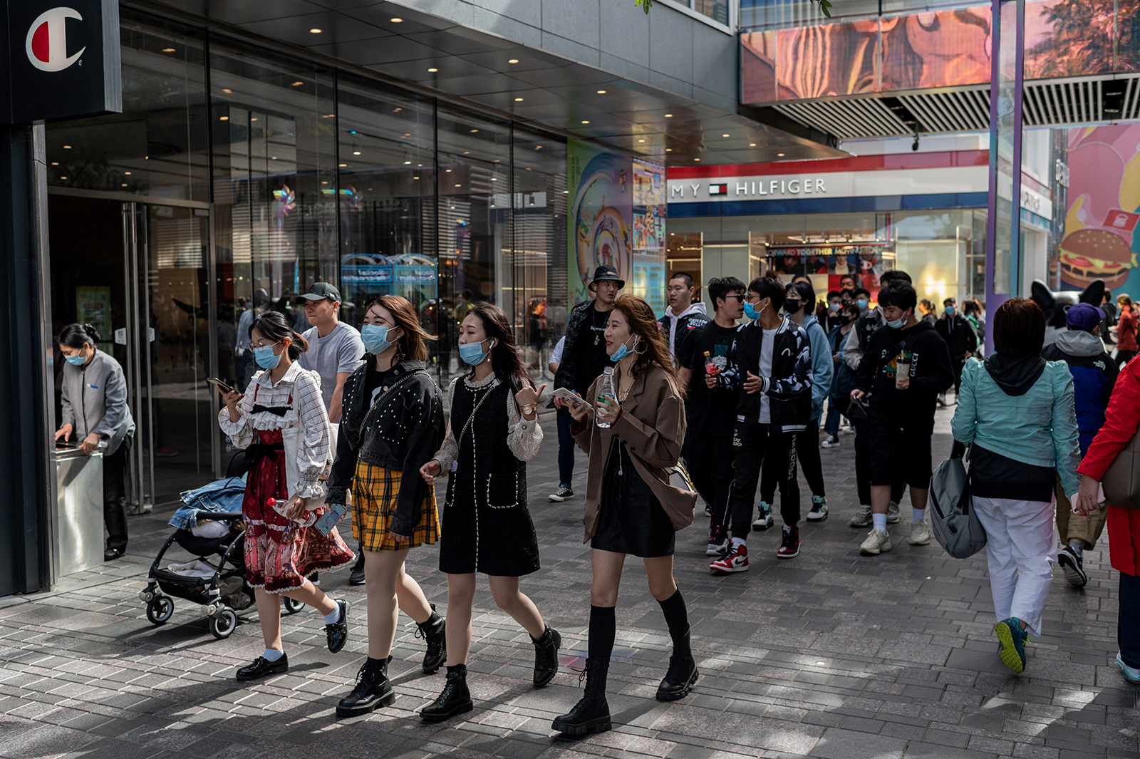 """People wearing face masks as a preventive measure against Covid-19 walk outside a shopping mall complex during the country's national """"Golden Week"""" holiday in Beijing, China on October 2."""