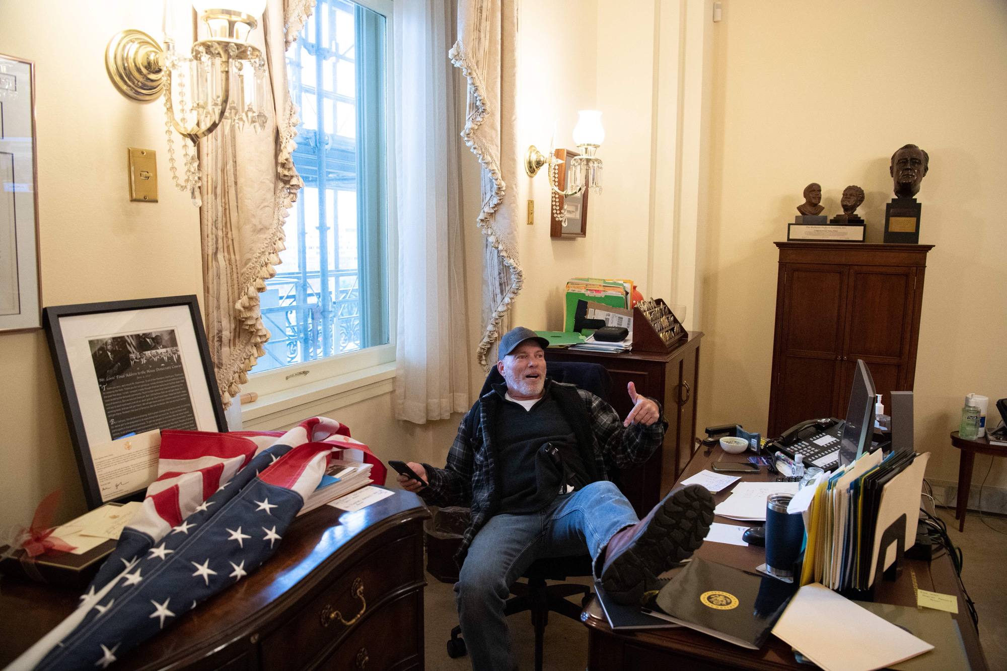 A Trump supporter sits inside the office of House Speaker Nancy Pelosi after breaching the Capitol in Washington, DC, on January 6.