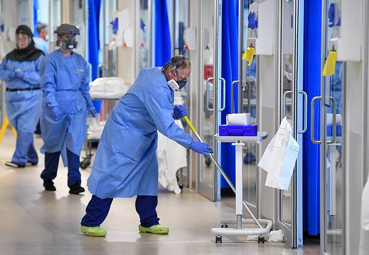 A worker mops a corridor in the Intensive Care unit at the Royal Papworth Hospital in Cambridge, UK, on Tuesday, May 5.
