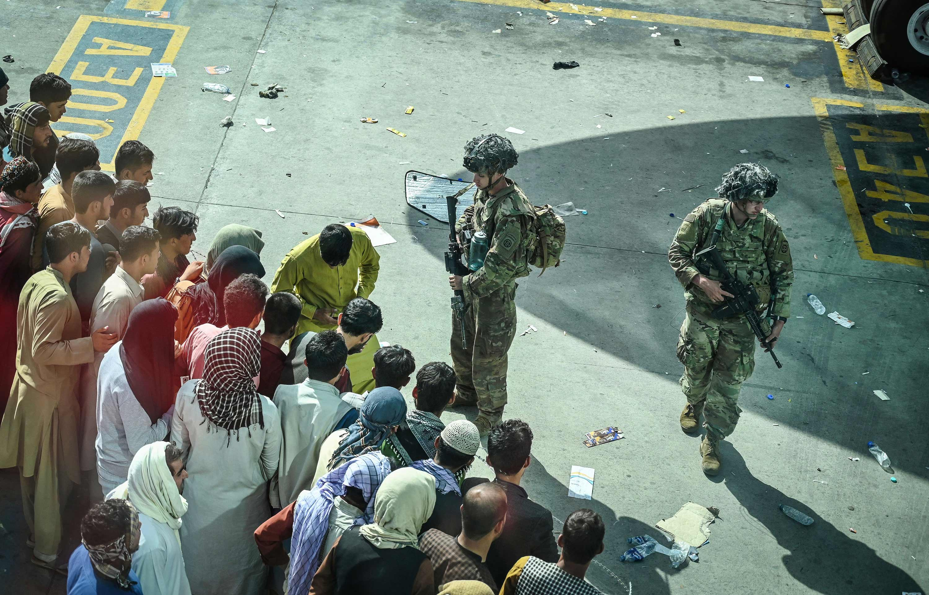 US soldiers stand guard as Afghan people wait at the Kabul airport on August 16.