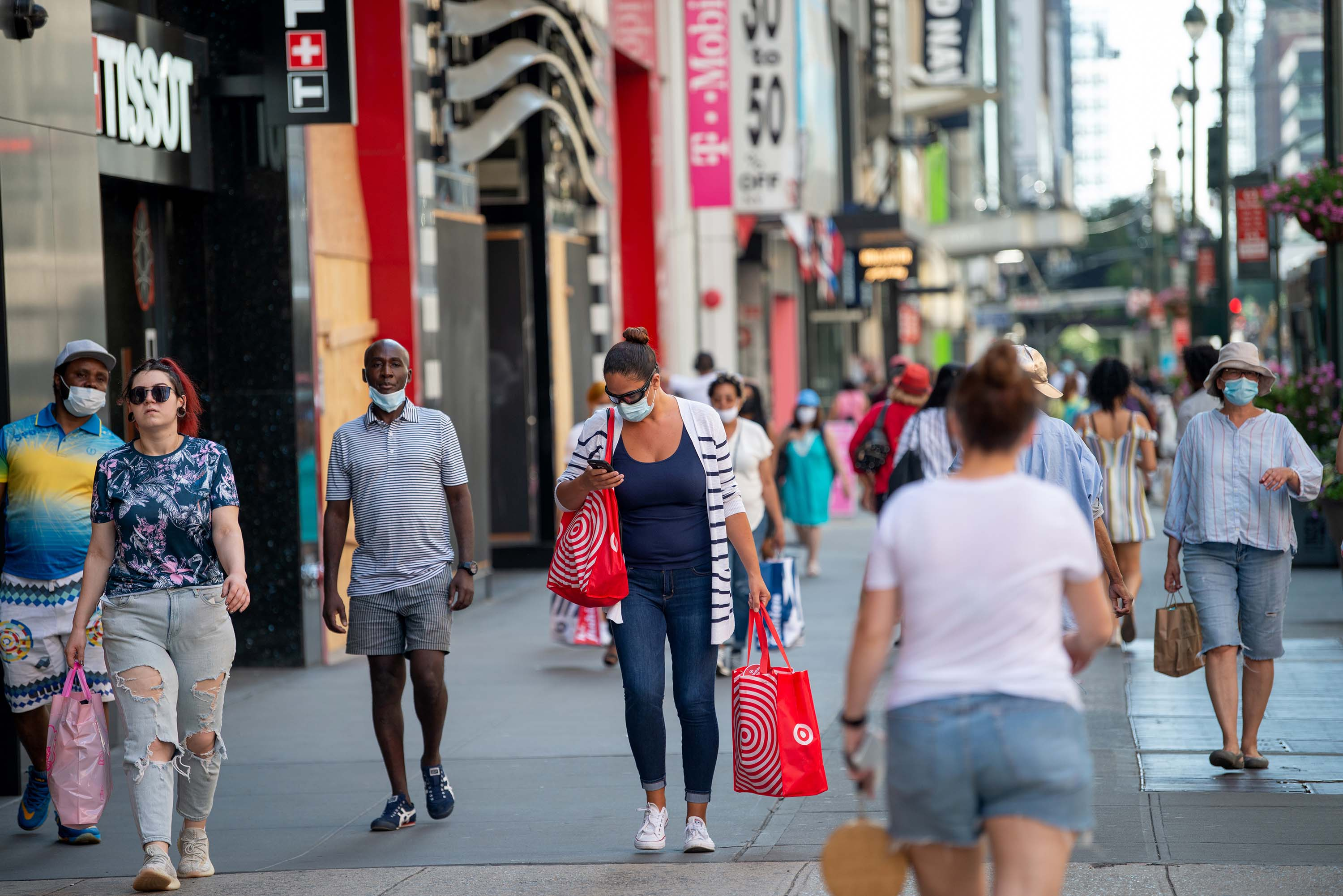 Pedestrians wearing face masks carry shopping bags in New York City on June 24.