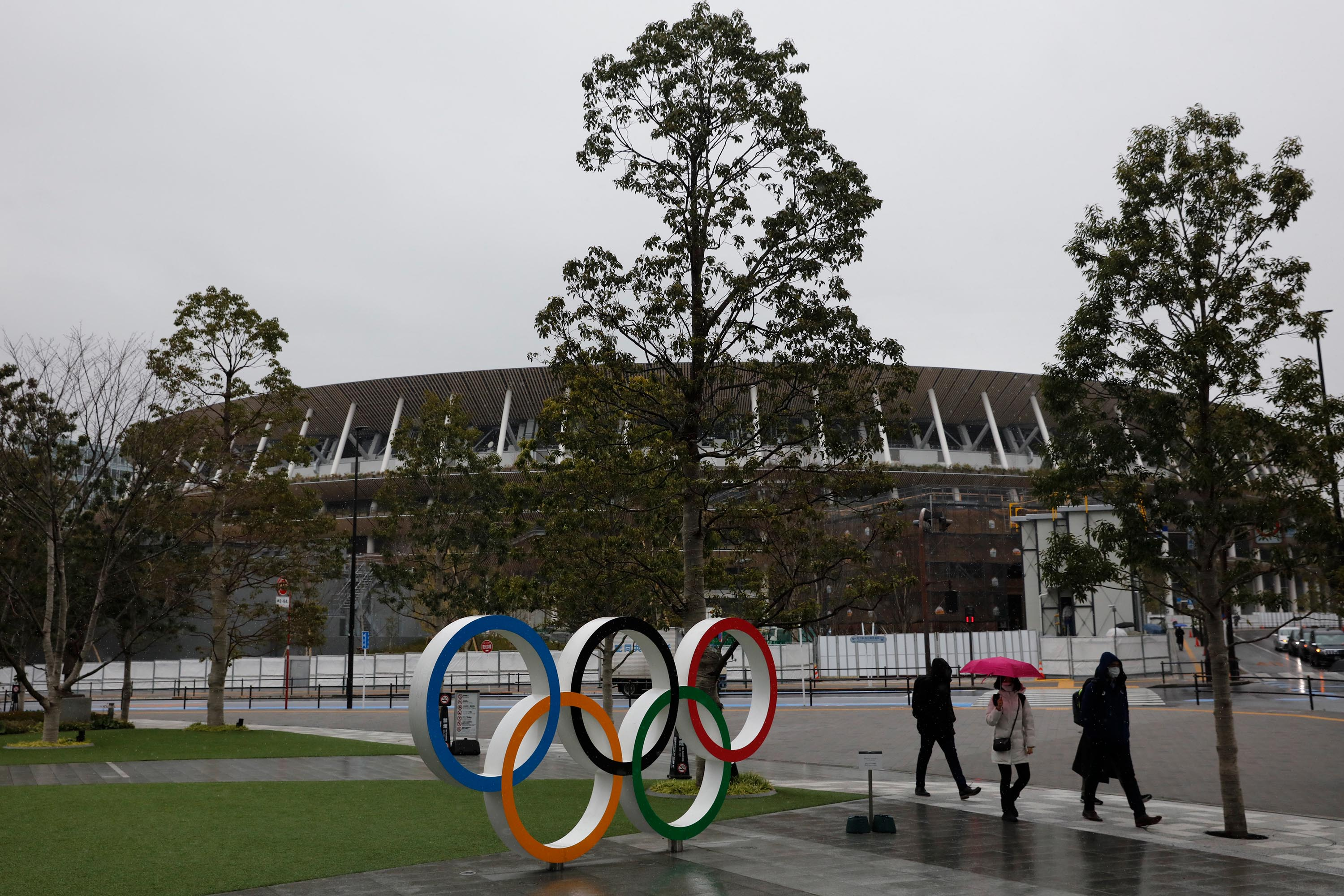 People walk past the Olympic rings near the New National Stadium in Tokyo, Wednesday, March 4.