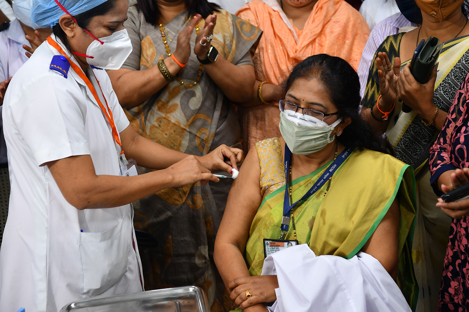 A medical worker inoculates Vidya Thakur, medical dean of the Rajawadi Hospital, with a Covid-19 vaccine at the hospital in Mumbai, India, on January 16.