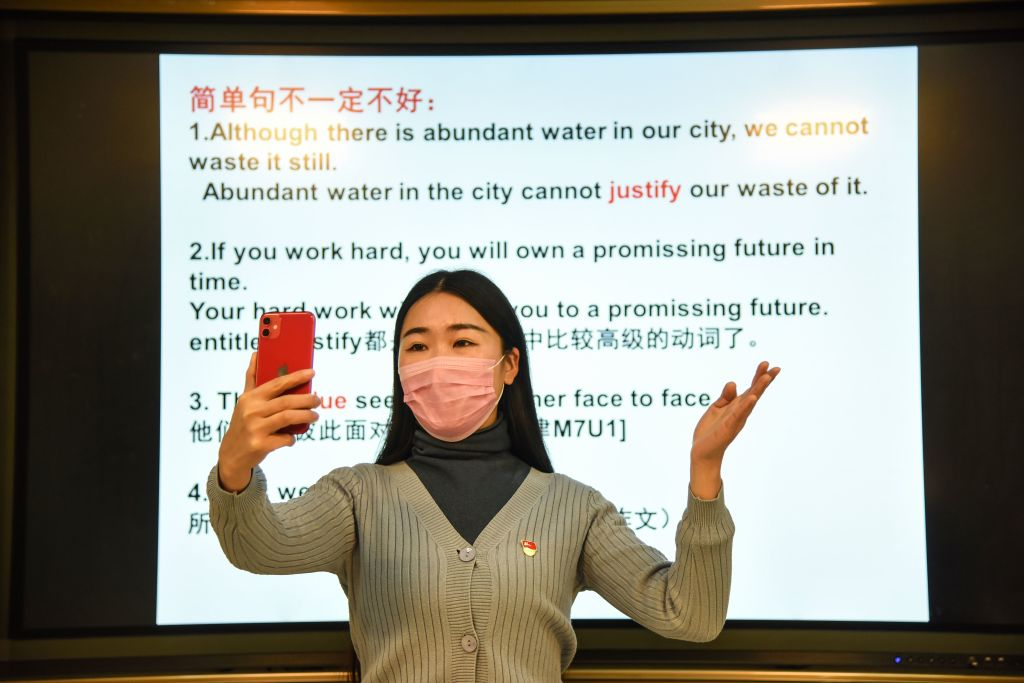 A teacher gives a lecture with her smart phone during an online class at a middle school in Donghai in China's eastern Jiangsu province on February 17, 2020.