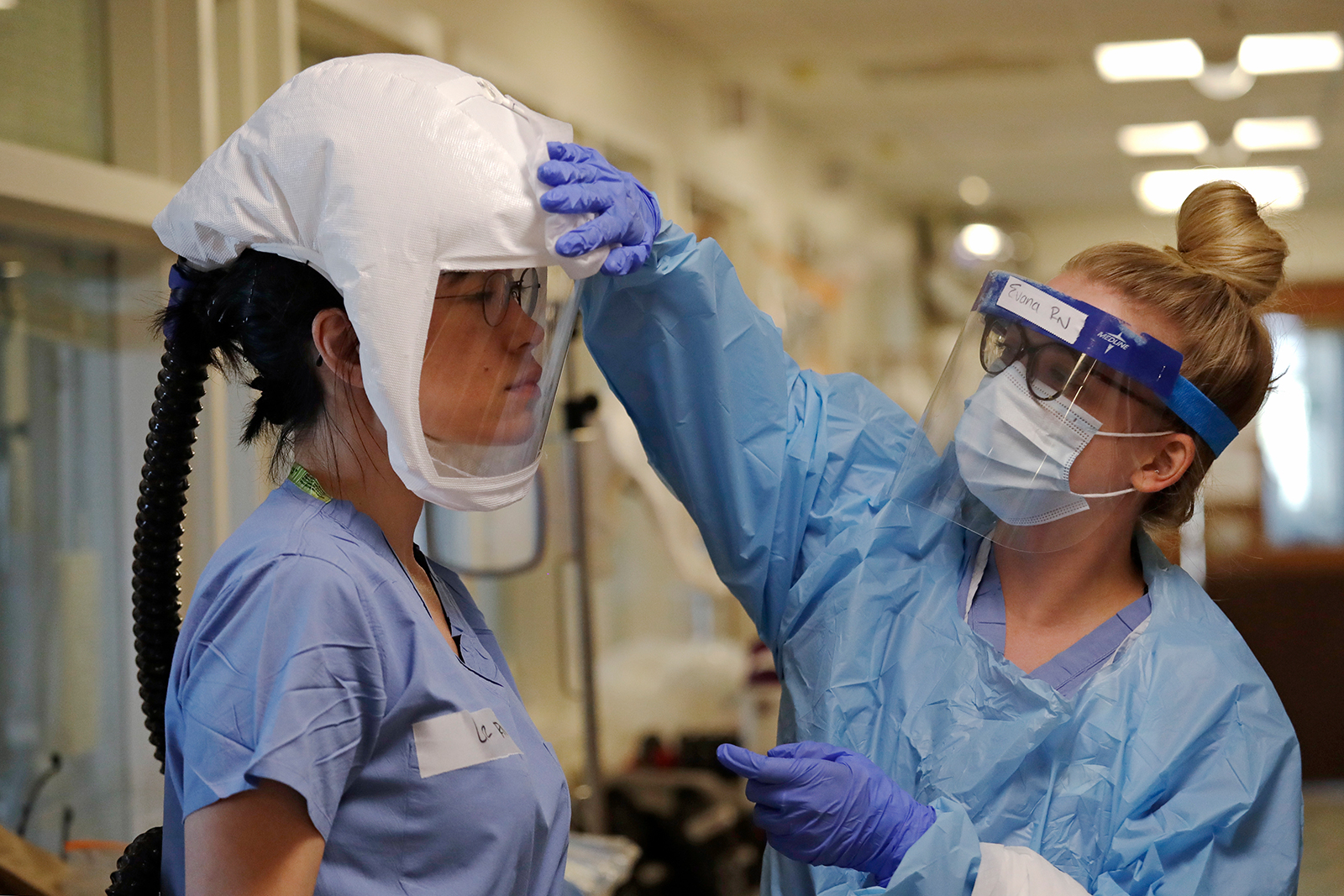 Liz Vereshko, left, is assisted into PPE equipment by fellow nurse Evana Croda before stepping into a patient's room in the Covid-19 Intensive Care Unit at Harborview Medical Center on May 8, in Seattle.