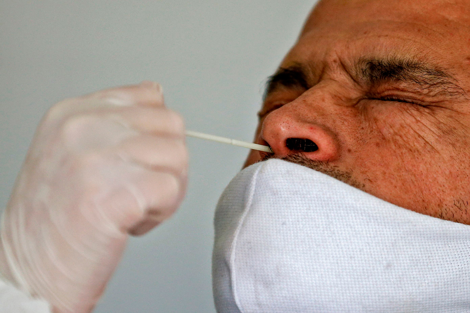 A health worker collects a nasal swab sample from a man to be tested for COVID-19 in Santiago, Chile, on Friday, July 10.