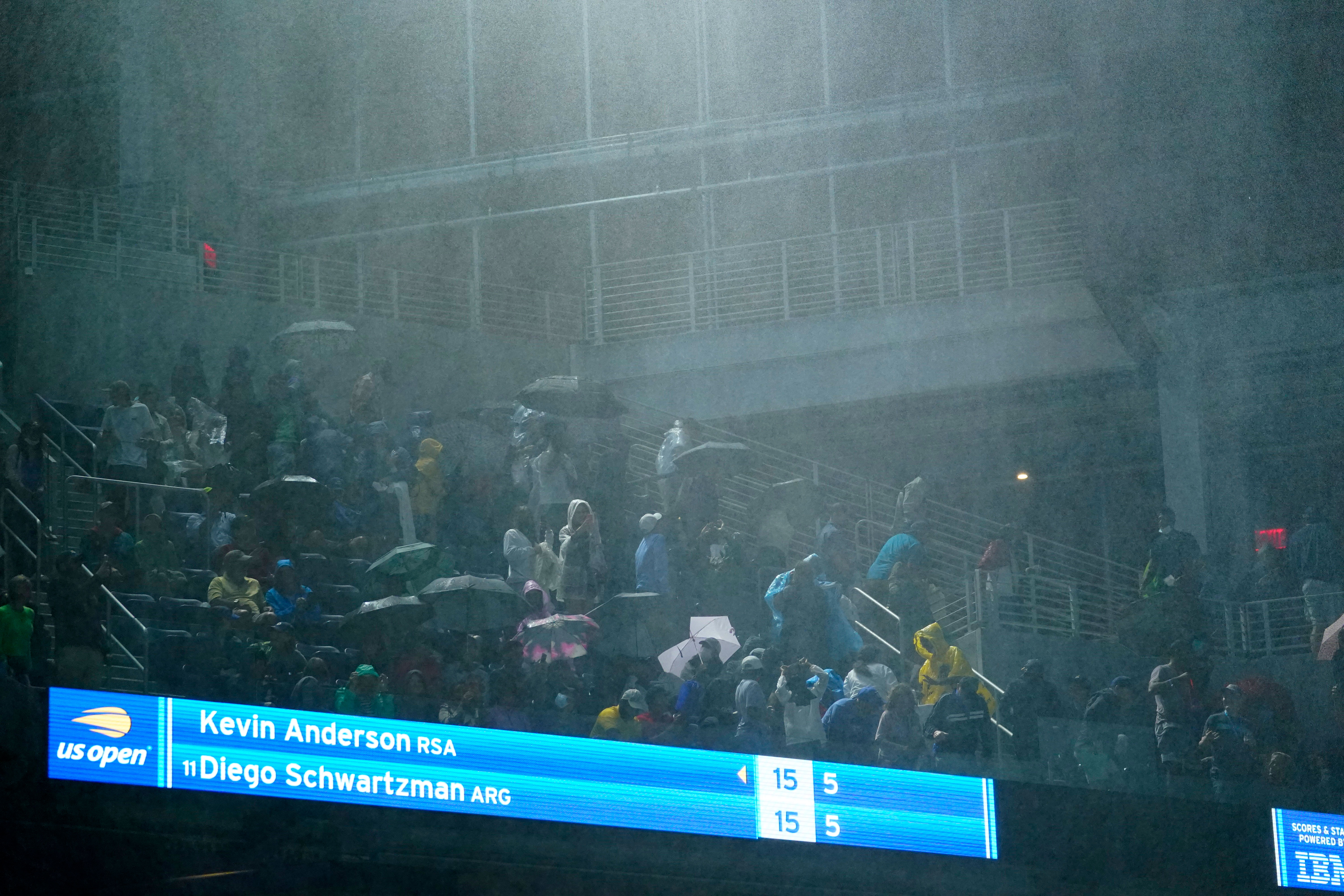 Rain falls into Louis Armstrong Stadium from the openings along the sides during a US Open tennis match between Diego Schwartzman and Kevin Anderson in Queens, New York, on September 1.