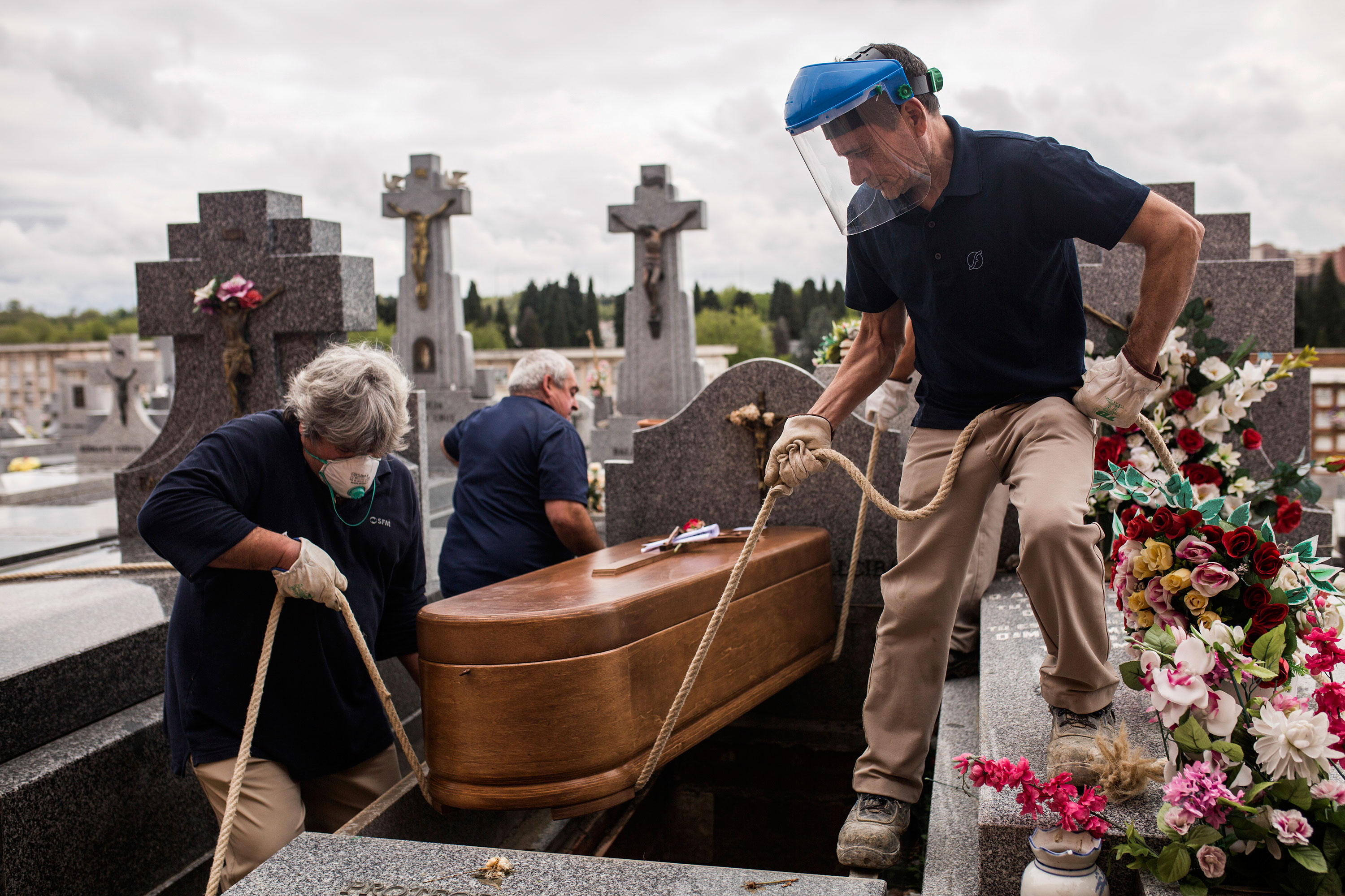 Undertakers lower a coffin at La Almudena cemetery in Madrid, Spain on April 7.