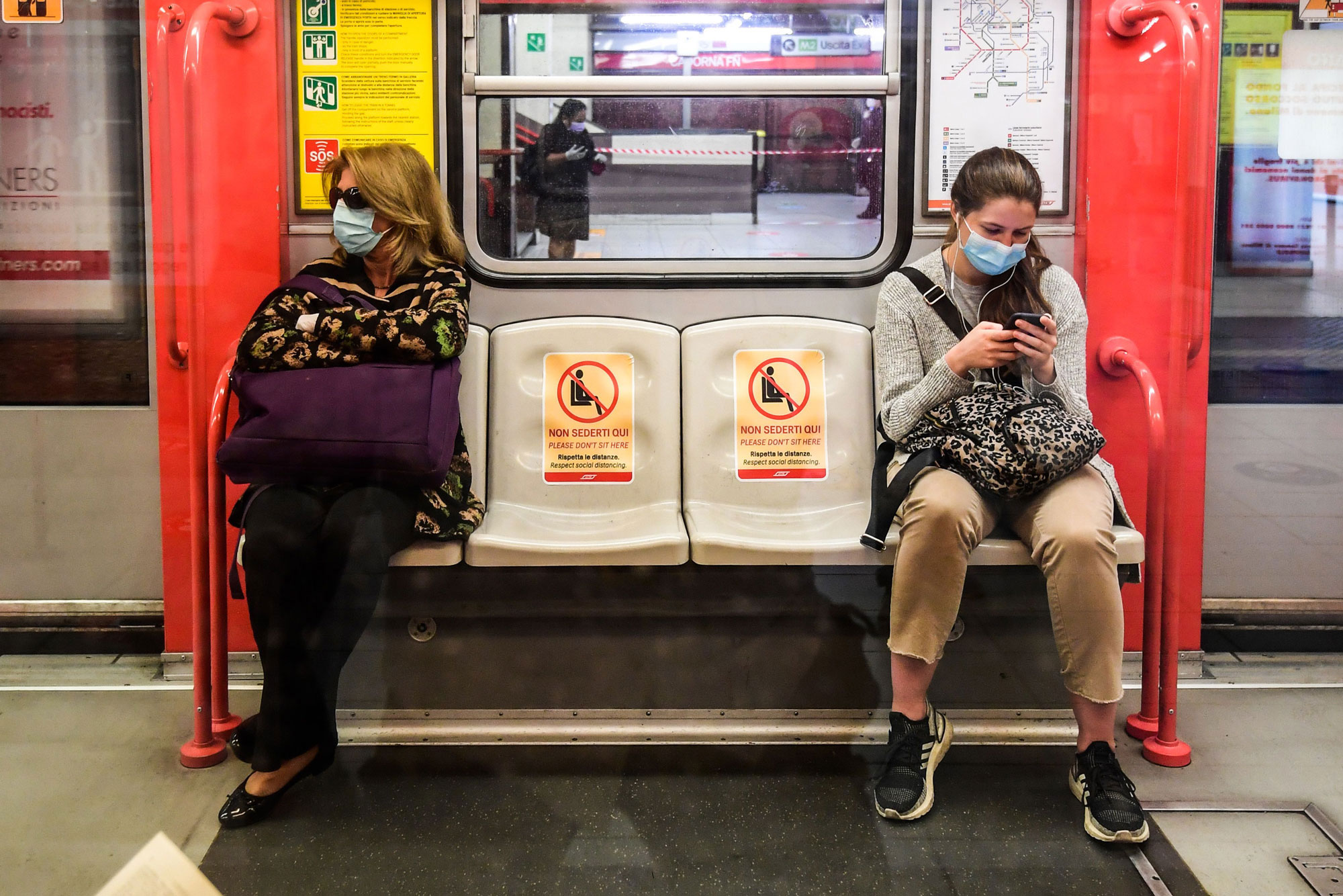 Commuters sit in a coach at the Cardona underground station in Milan, Italy, on May 4.