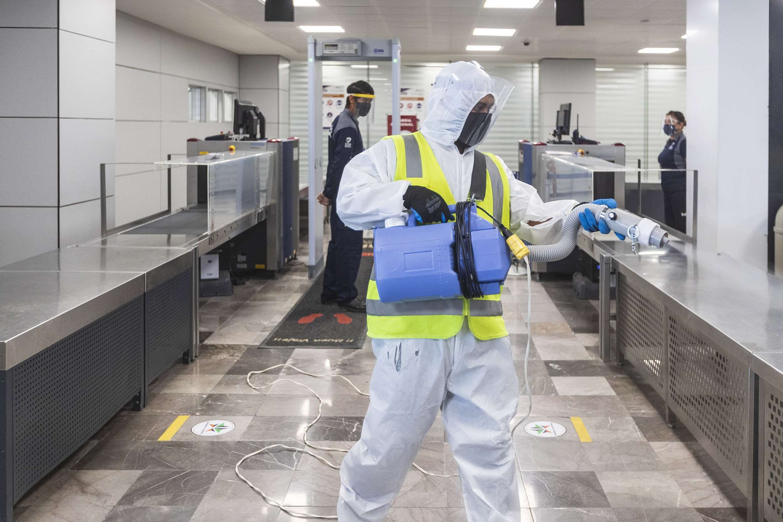 A sanitation worker wearing personal protection equipment cleans and disinfect the checkpoint at Manuel Márquez de Léon International Airport on July 17, 2020 in La Paz, Mexico.