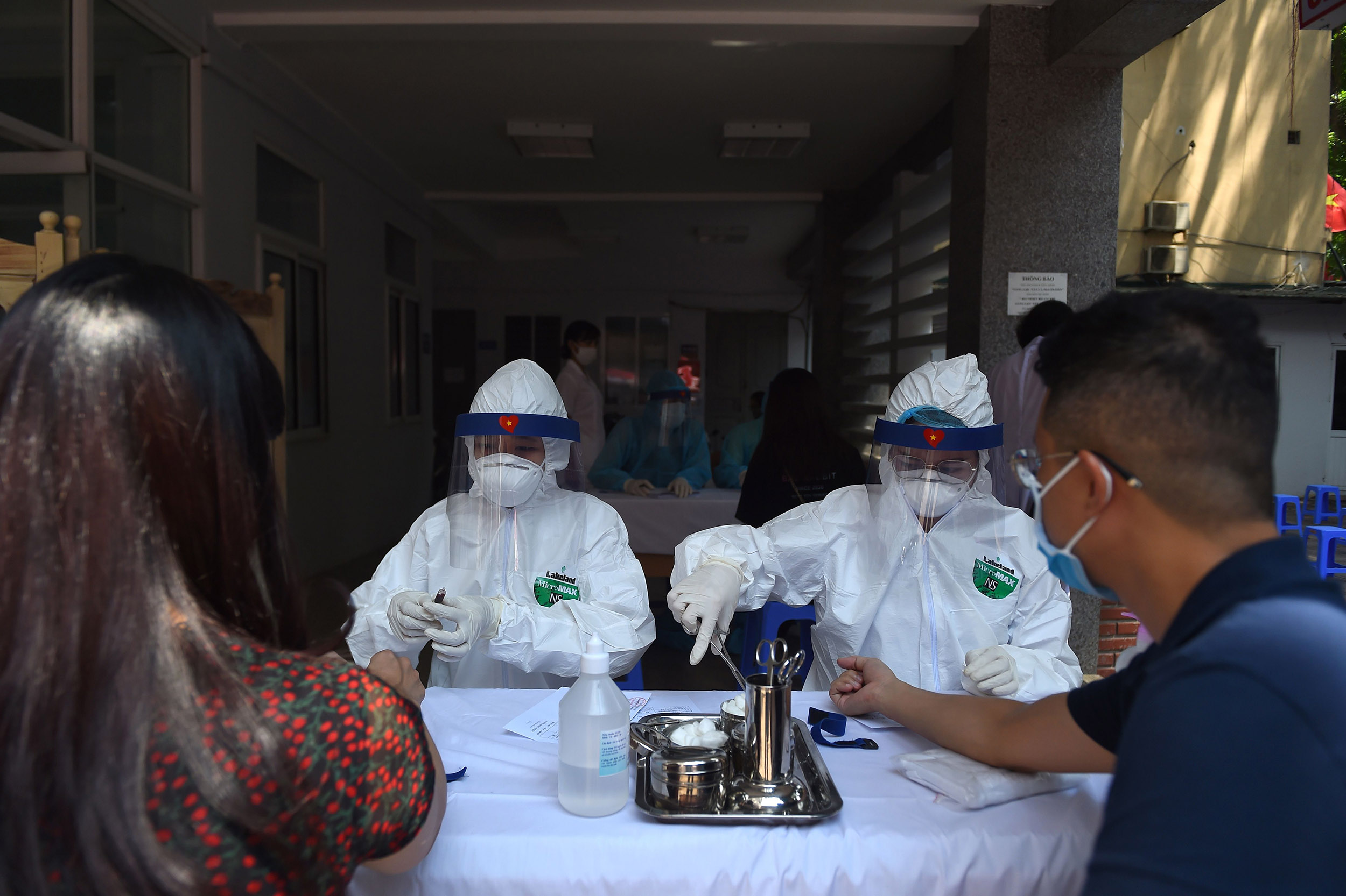 Residents get blood samples taken by health workers at a Covid-19 rapid testing site in Hanoi, Vietnam, on July 30.