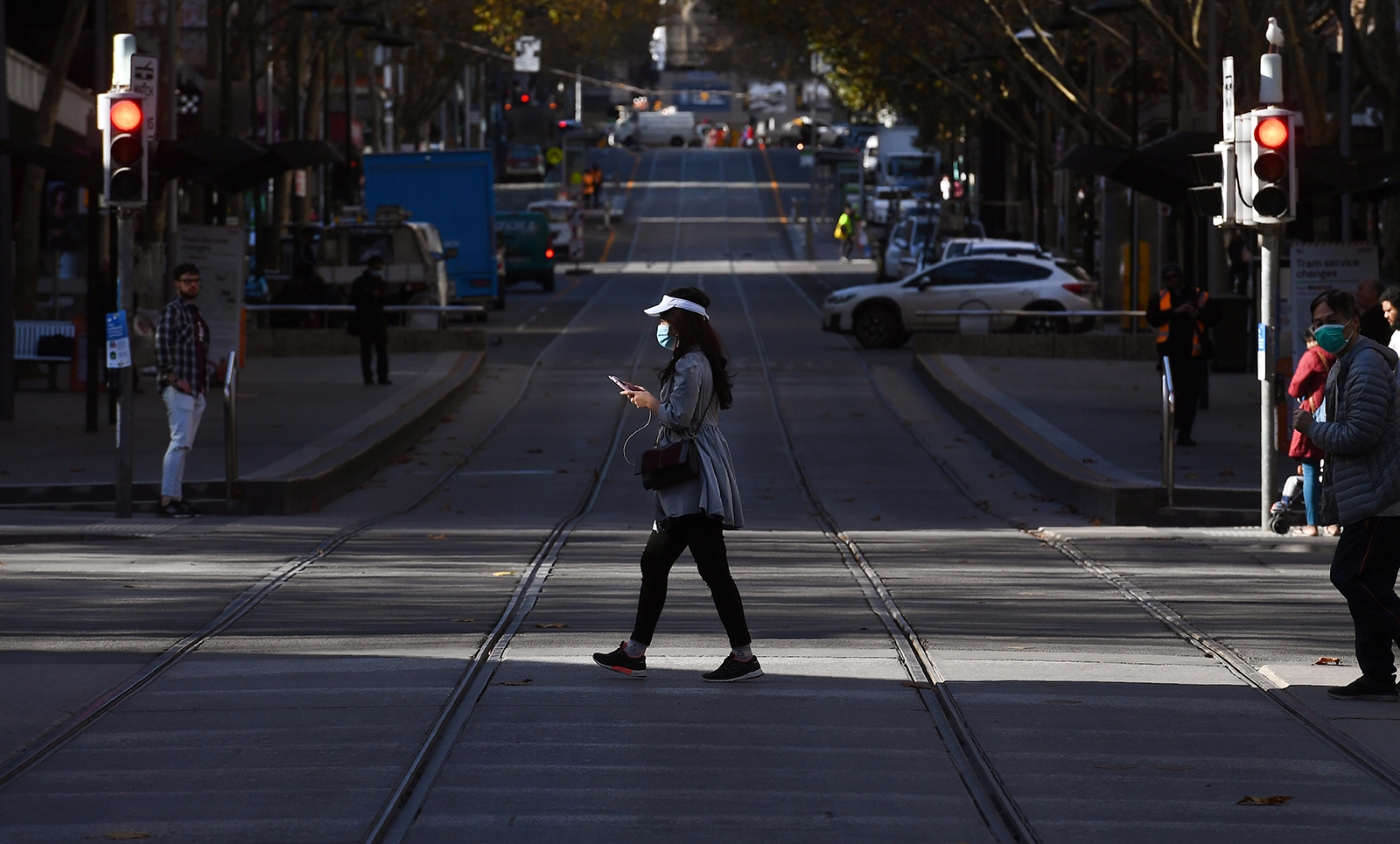 A woman crosses a street in Melbourne's central business district on June 17.