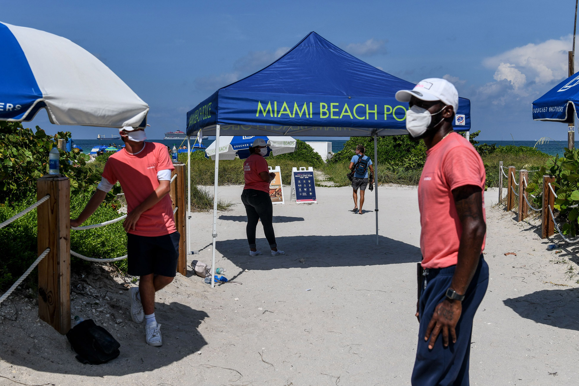 """""""Social distancing ambassadors"""" wearing pink stand at the entrance to Miami Beach, Florida, on June 10."""