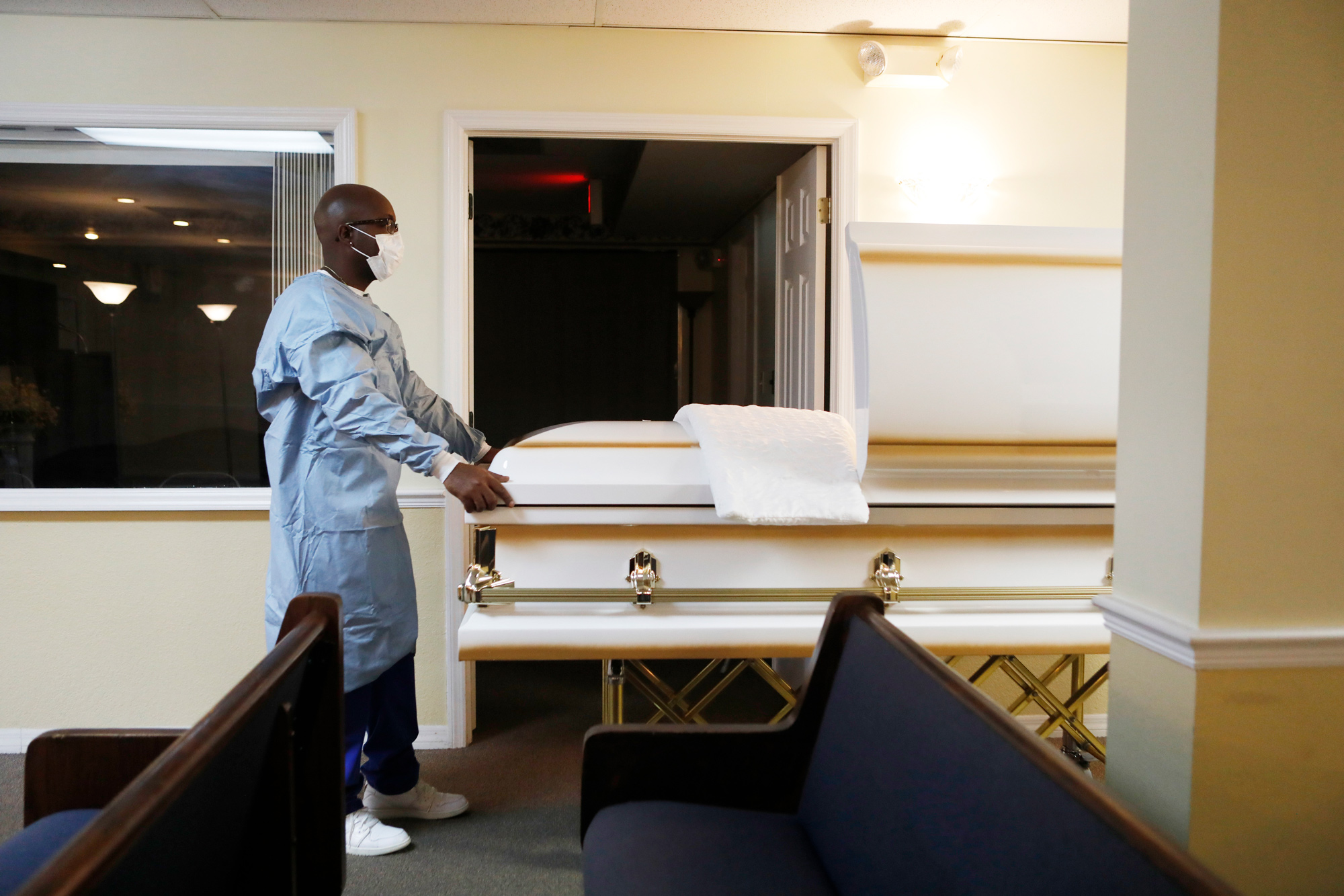 A mortician assistant prepares a funeral service for a man who died of COVID-19 at Ray Williams Funeral Home on August 12 in Tampa, Florida.