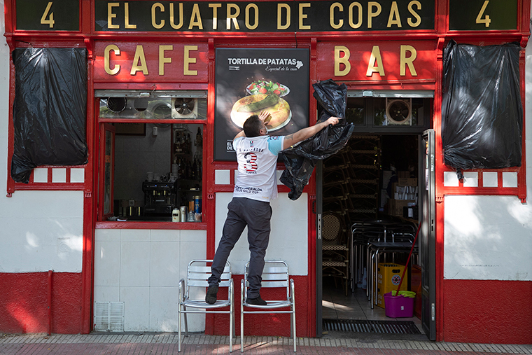 A worker uncovers the front of a bar preparing to reopen in Madrid, Spain, Monday, May 25.