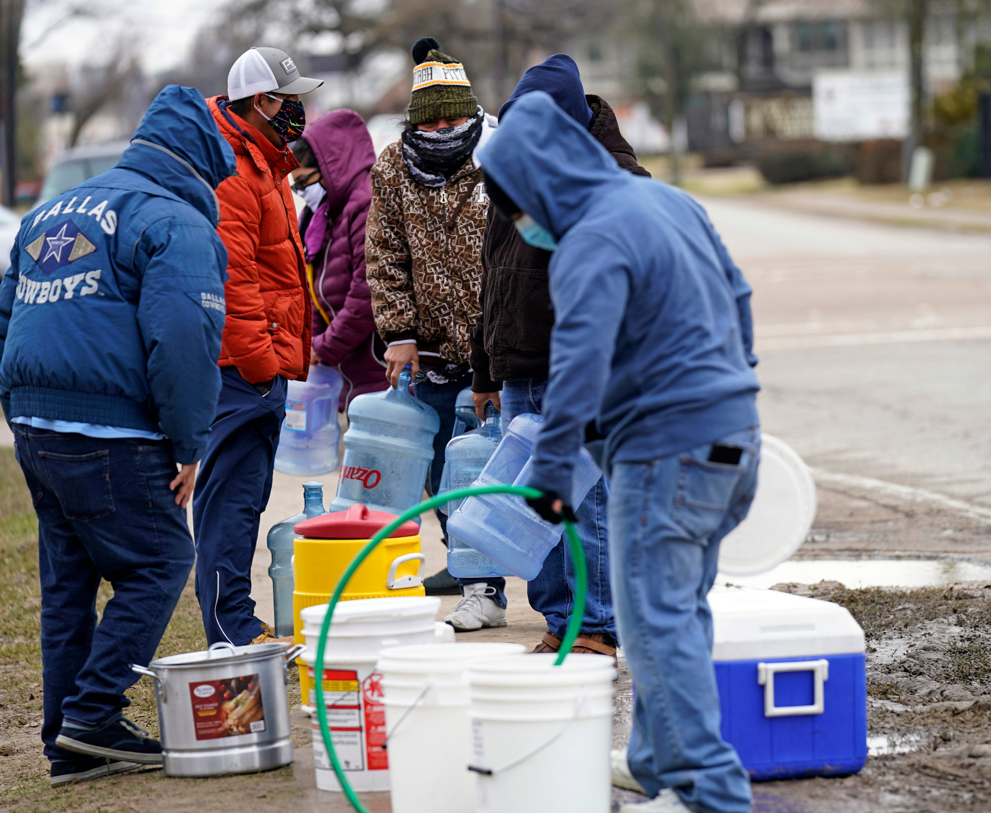 People wait in line to fill containers with water from a park spigot on February 18 in Houston, Texas.