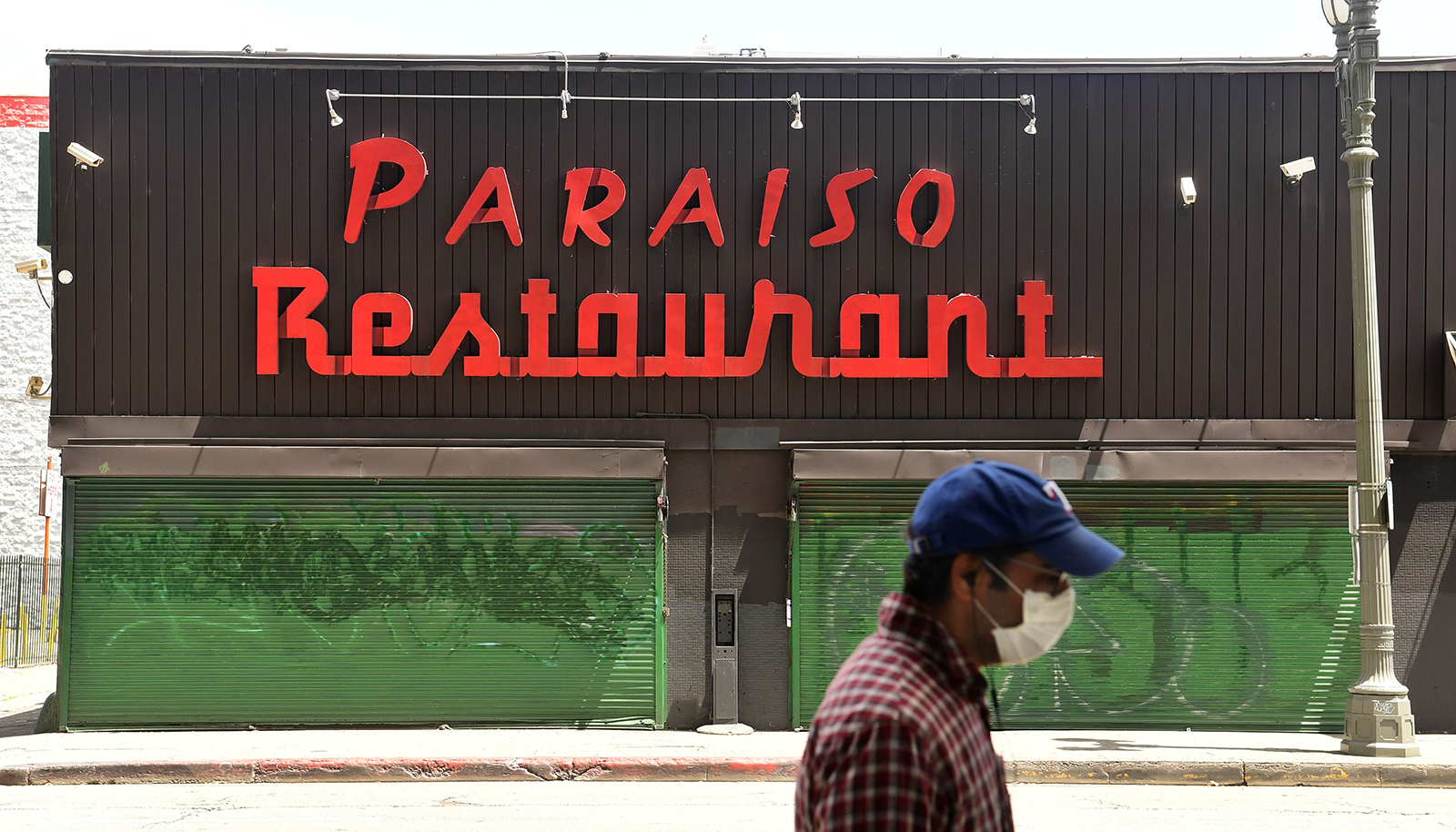 A pedestrian wearing a face mask walks passed a closed Paraiso Restaurant in Los Angeles, on May 7.