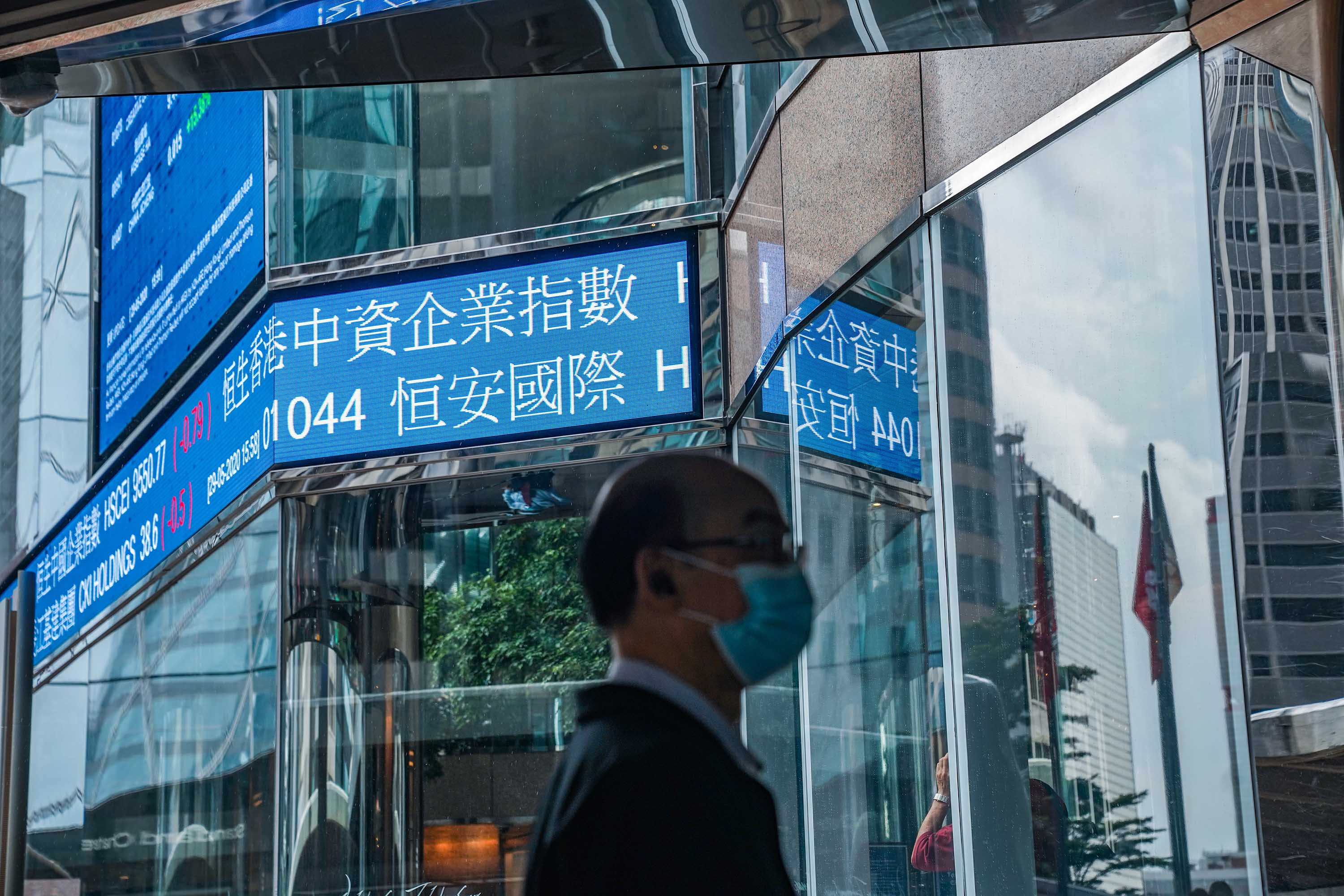 A pedestrian walks past a stock ticker at the Exchange Square complex, which houses the Hong Kong Stock Exchange, in Hong Kong on May 29.