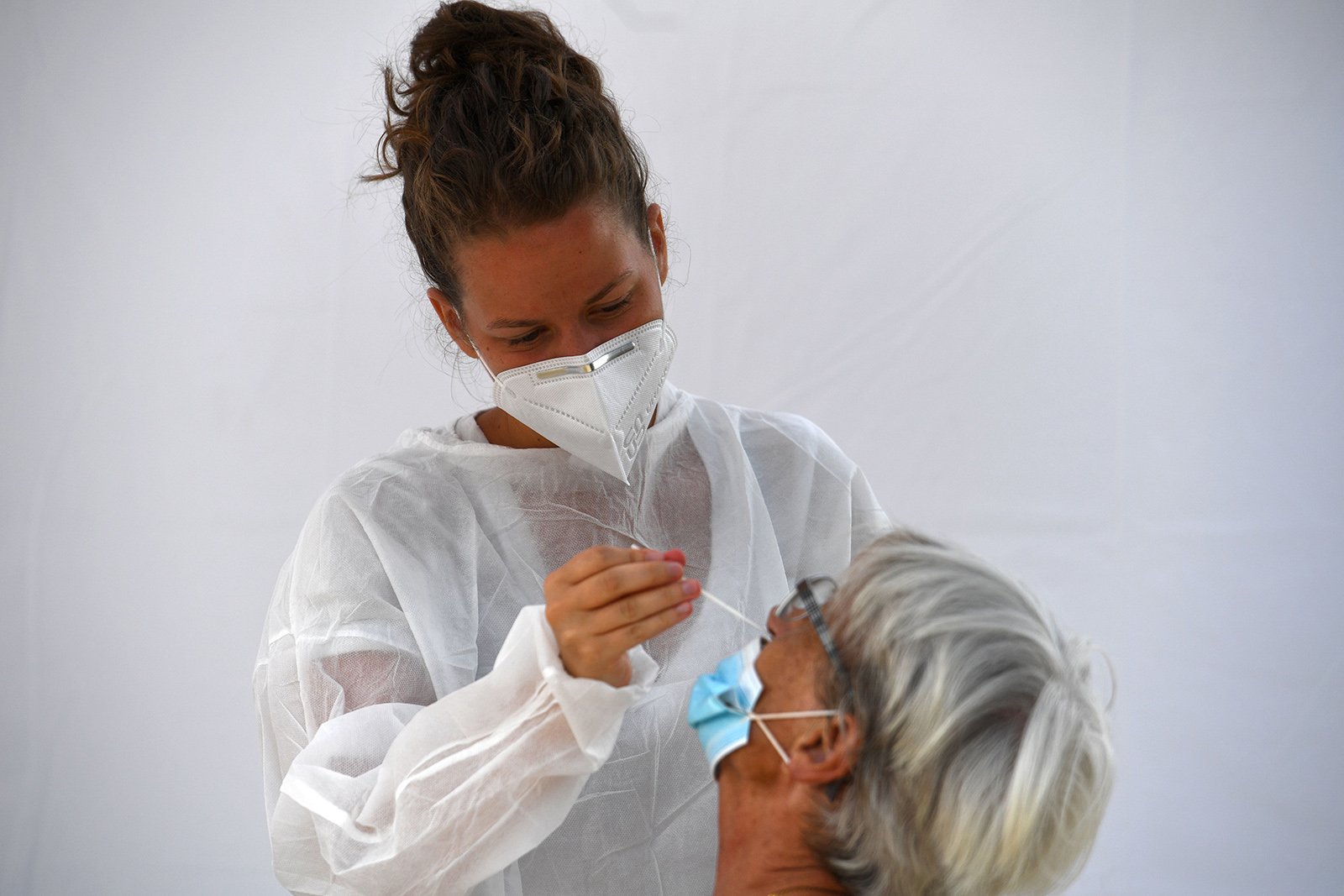 A medical staff member collects a swab sample from a woman at a Covid-19 testing site in Saint-Nic, France, on August 12.