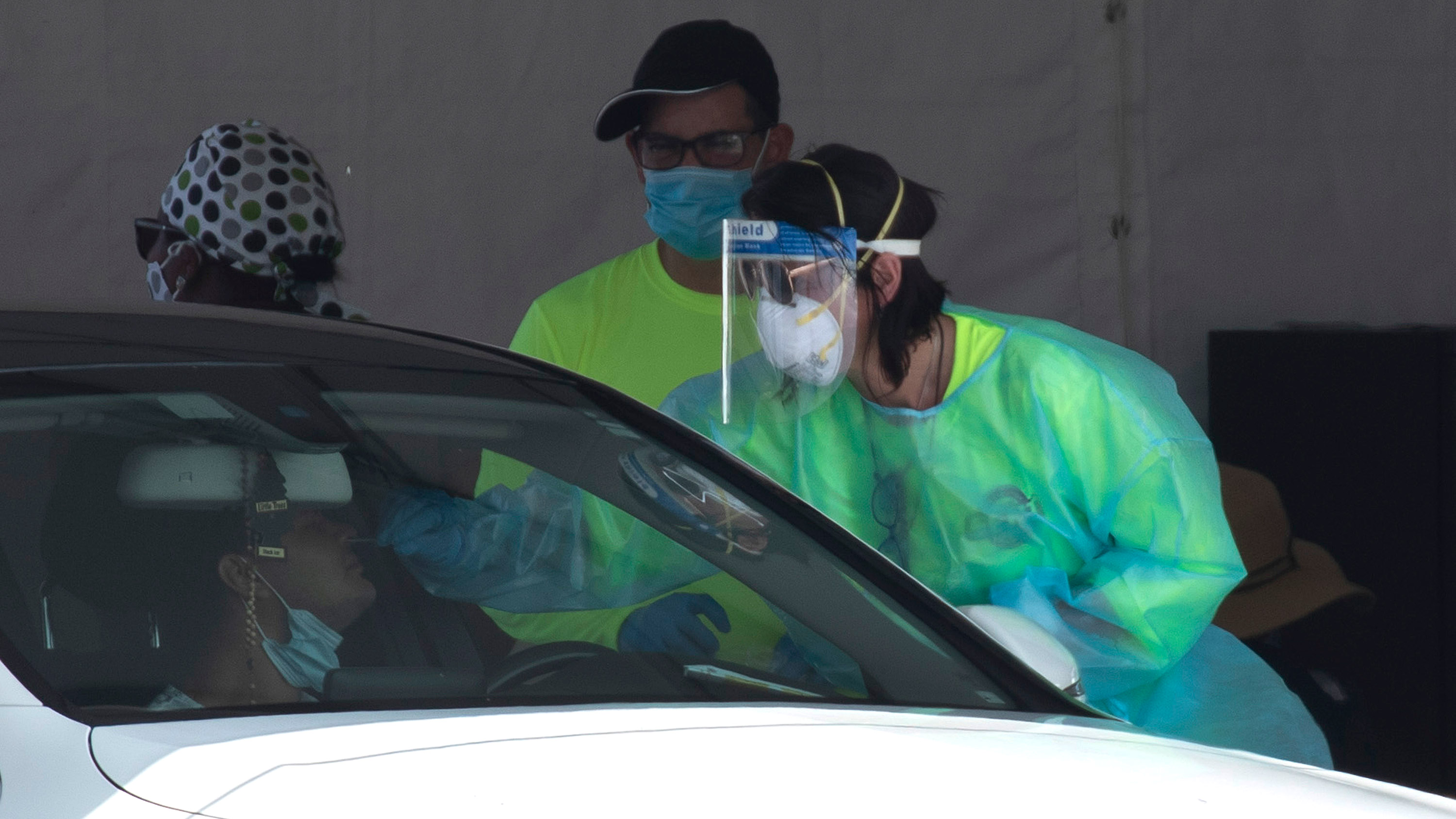 A health care worker tests a person for COVID-19 at the test site located in the Hard Rock Stadium parking lot on July 15 in Miami Gardens, Florida.