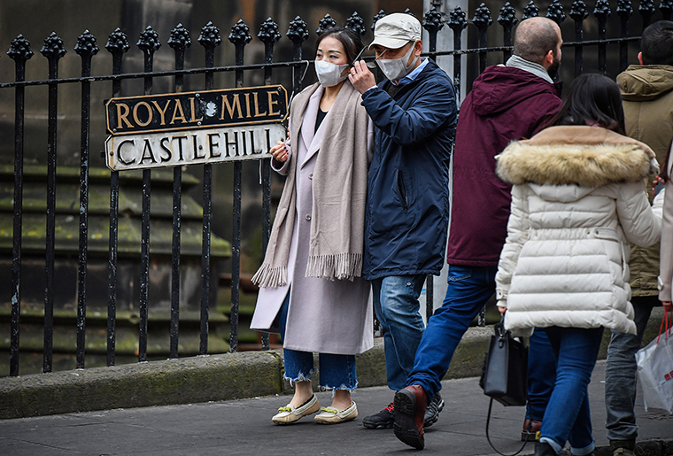 Tourists wear face masks as they visit Edinburgh Castle on January 24, in Edinburgh, Scotland.