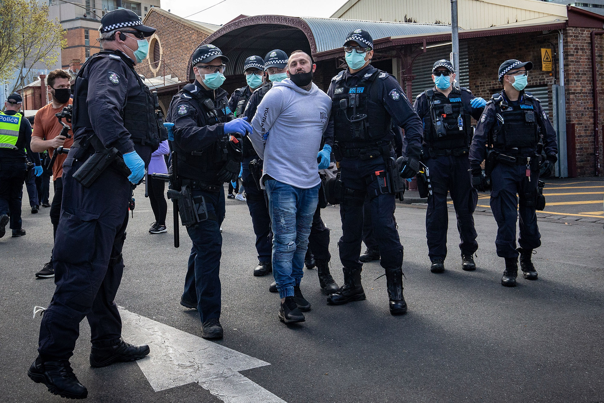 "A man is detained by police on Sunday in Melbourne after anti-lockdown protesters organized a ""freedom walk"" to demonstrate against Covid-19 restrictions."