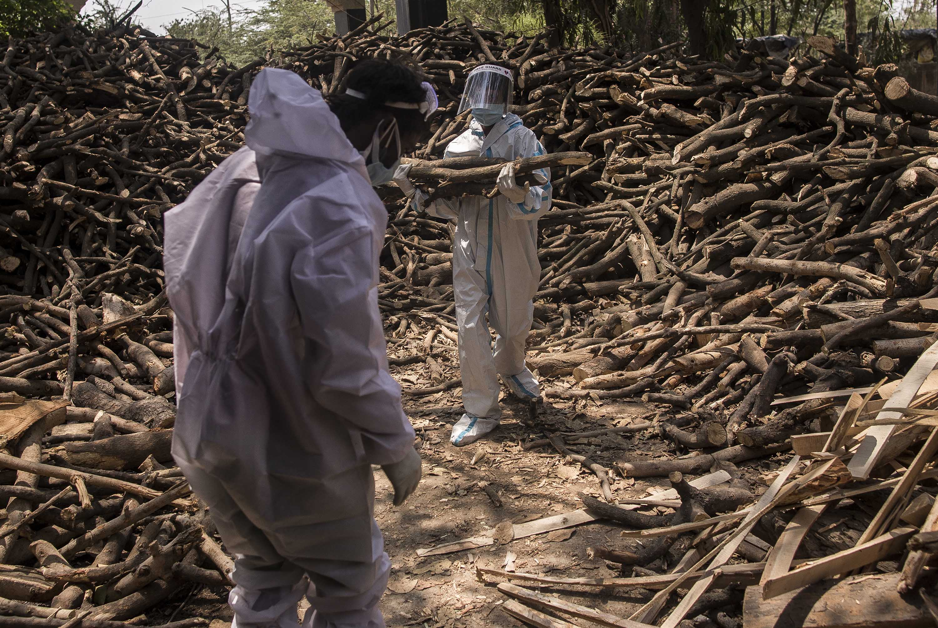 Workers sort logs of wood to be used on funeral pyres for people who died of Covid-19, at a crematorium on the outskirts of New Delhi, India, on April 22.