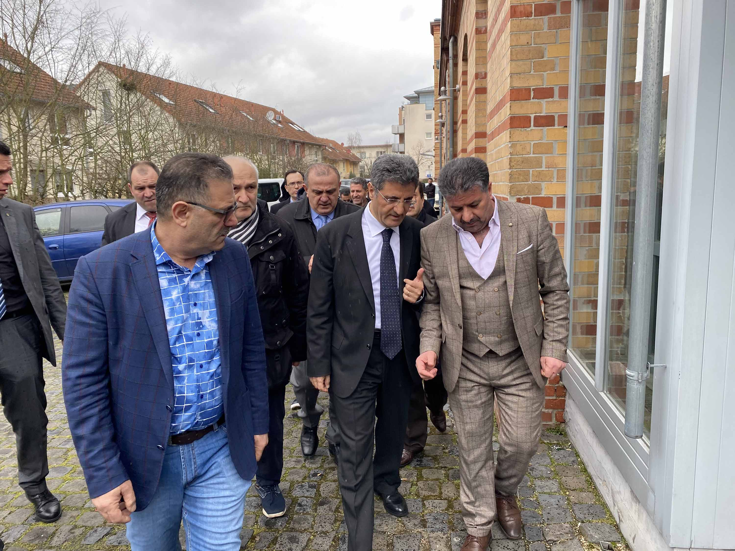 Turkey's Ambassador to Berlin, Ali Kemal Aydin, second from right, gathers with citizens near the scene of the shootings in Hanau, Germany on Thursday.