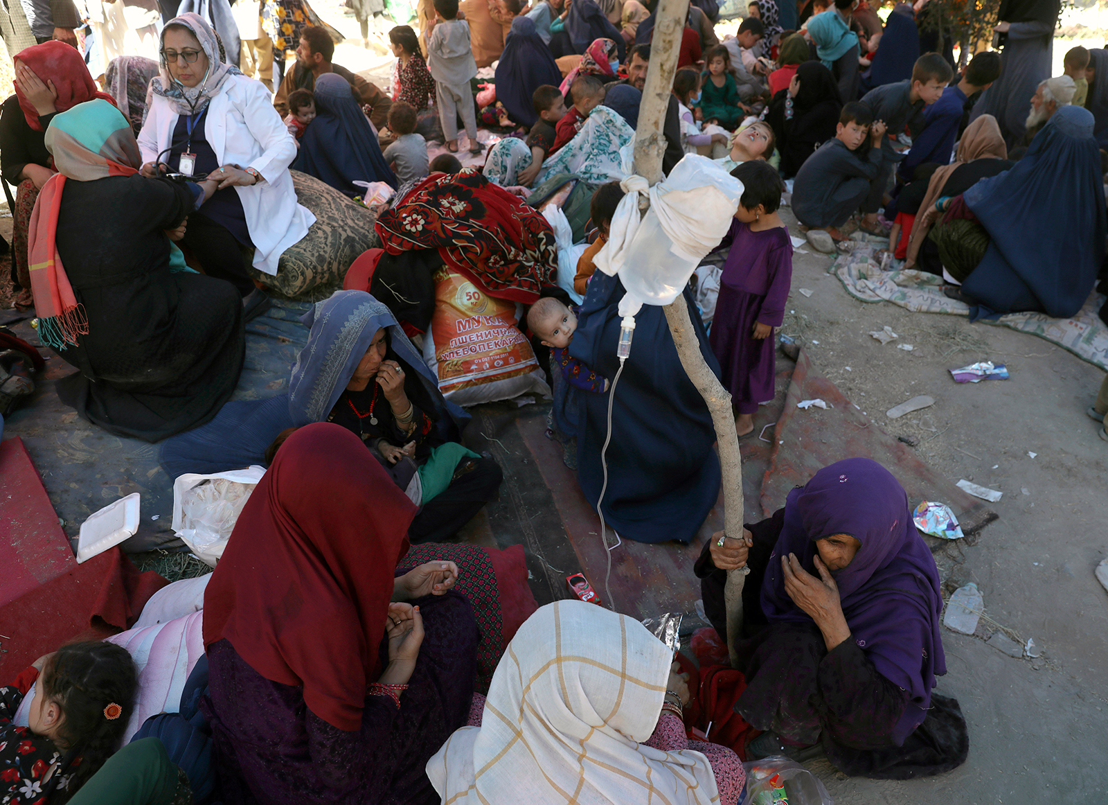 Internally displaced Afghan women from northern provinces, who fled their home due to fighting between the Taliban and Afghan security personnel, receive medical care in a public park in Kabul on August 10.