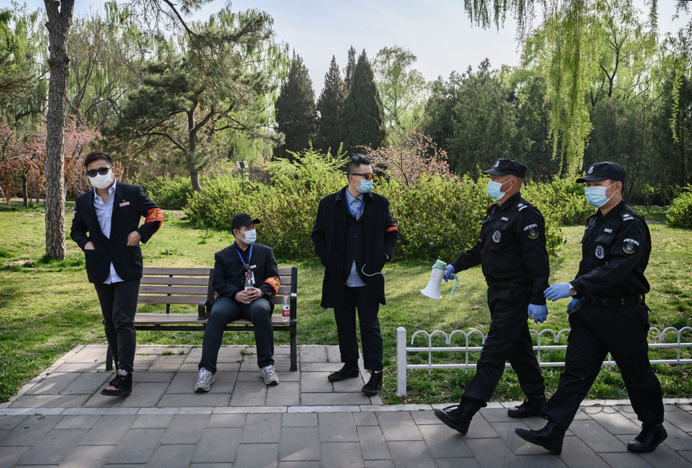 Security guards and park workers wear protective masks on April 5 at a park in Beijing, China.
