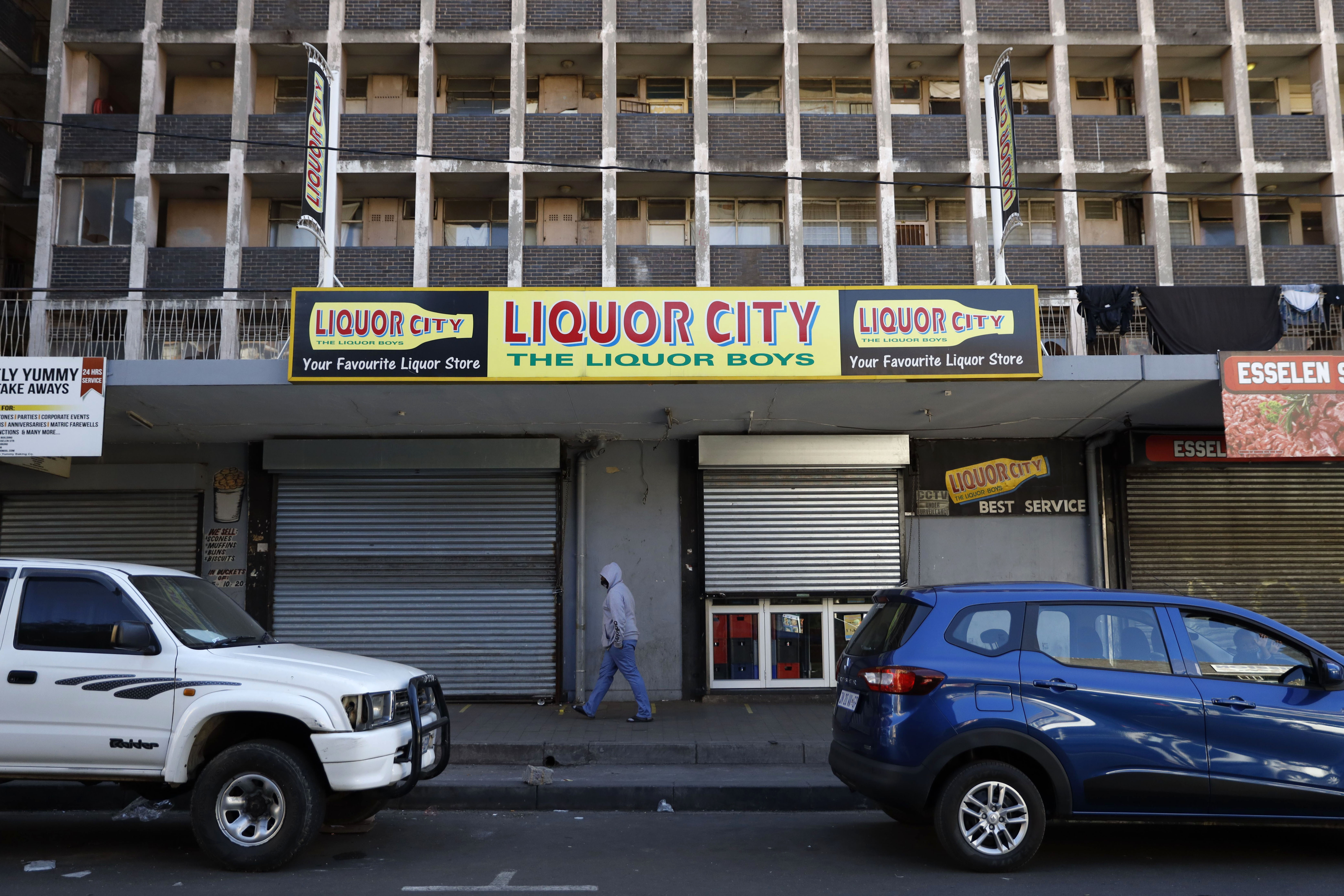A person walks by a closed liquor shop in the Hillbrow neighborhood of Johannesburg, South Africa, on July 13.