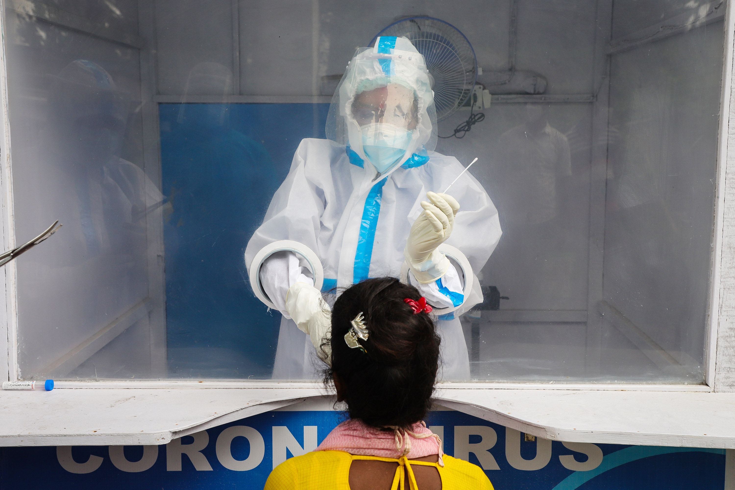 Health workers wearing PPE collect swab samples of people from inside a new Covid-19 testing kiosk in a hospital.