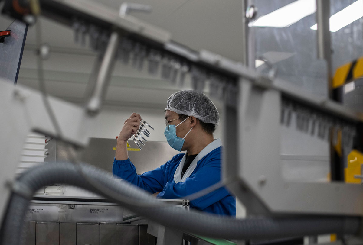 A worker checks syringes of Sinovac Biotech's potential Covid-19 vaccine, CoronaVac, on the production line during a media tour on September 24 in Beijing, China.