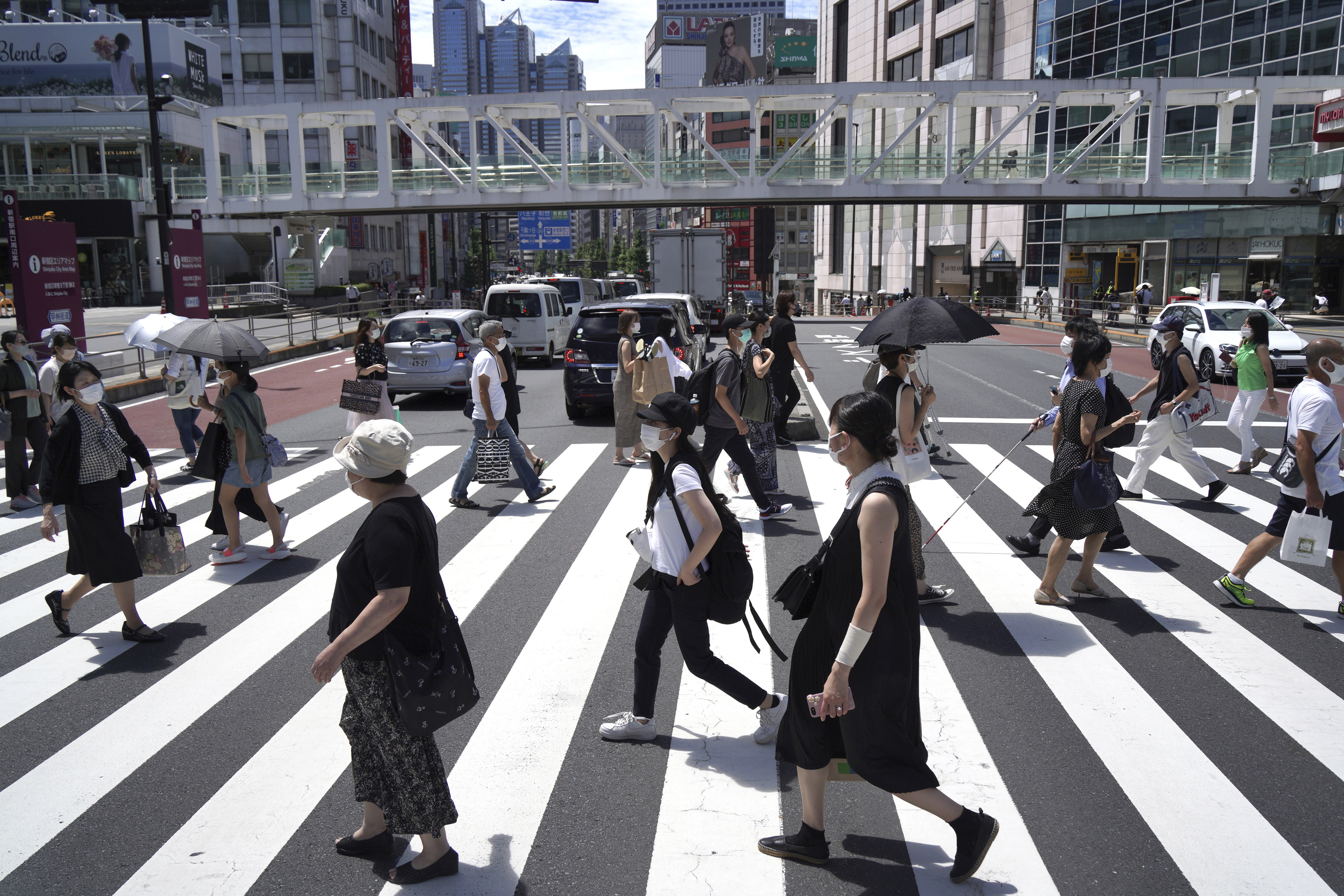 People cross a street in the Shinjuku district of Tokyo on Friday.