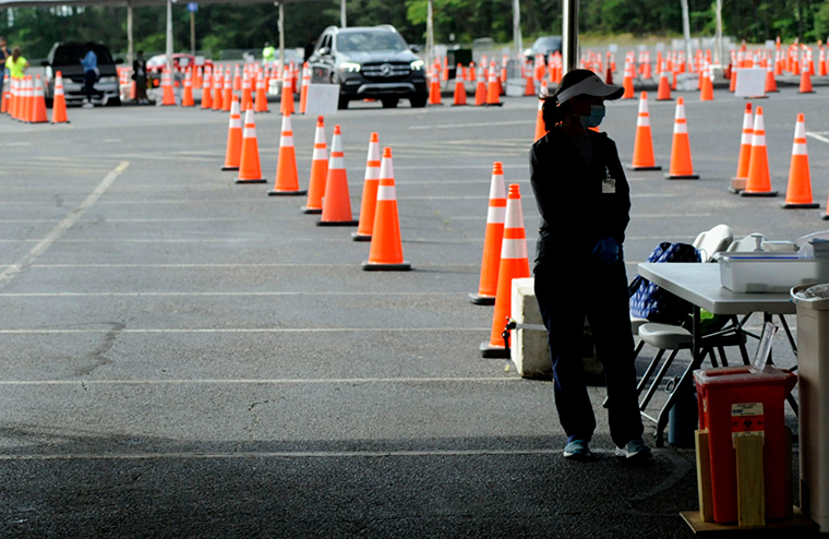 A worker from the University of Alabama at Birmingham waits for patients to arrive on Tuesday, May 18, at a mass COVID-19 immunization site in Hoover, Alabama, where declining demand prompted a shutdown.