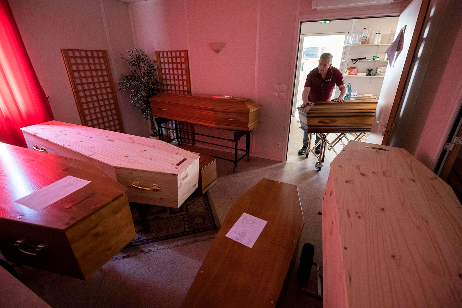 An employee at Lance Funeral Company wheels a coffin of a coronavirus victim into a storage room in Mulhouse, France on April 5.