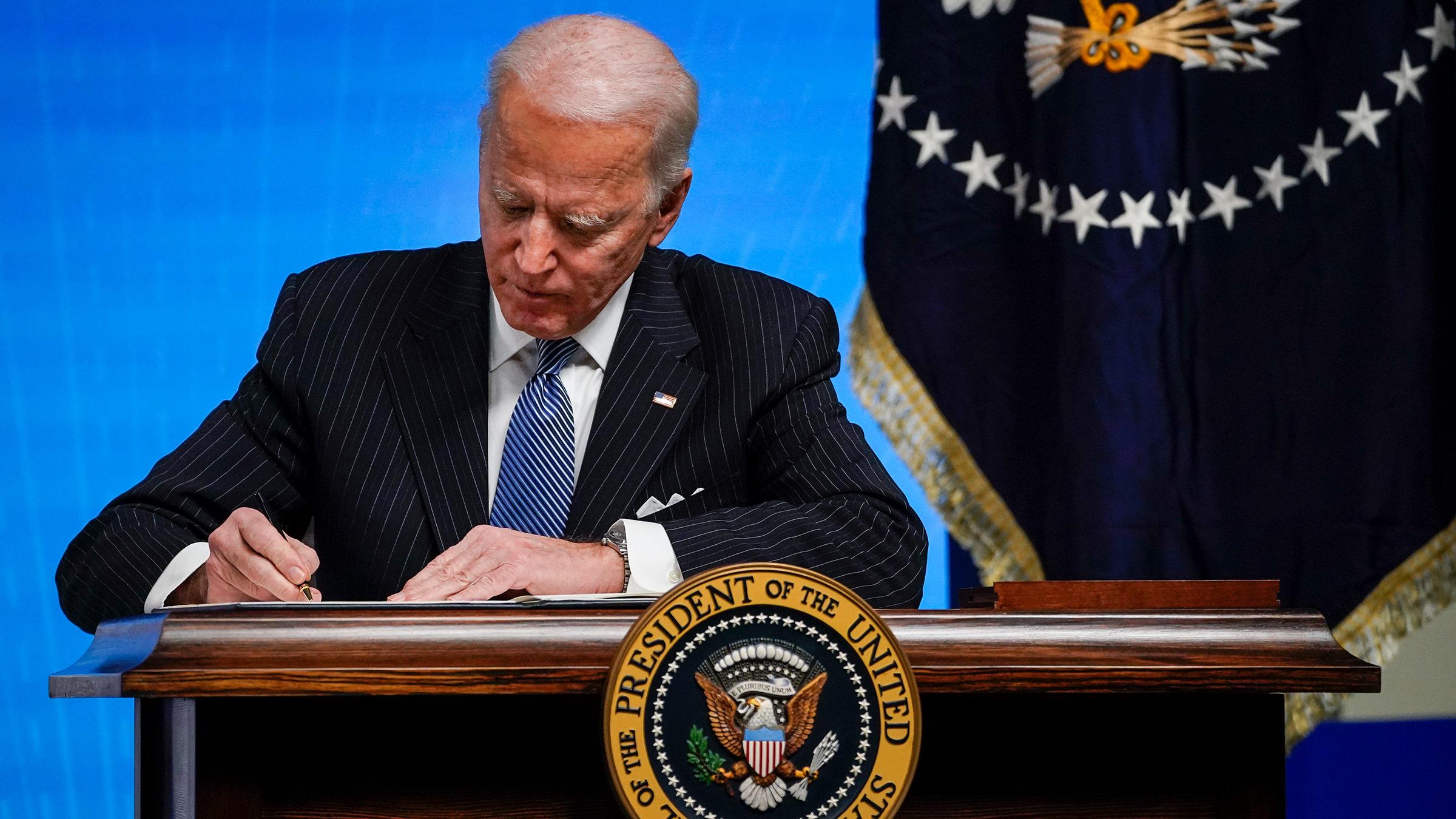 President Joe Biden signs an executive order on Monday, January 25, in Washington, DC.