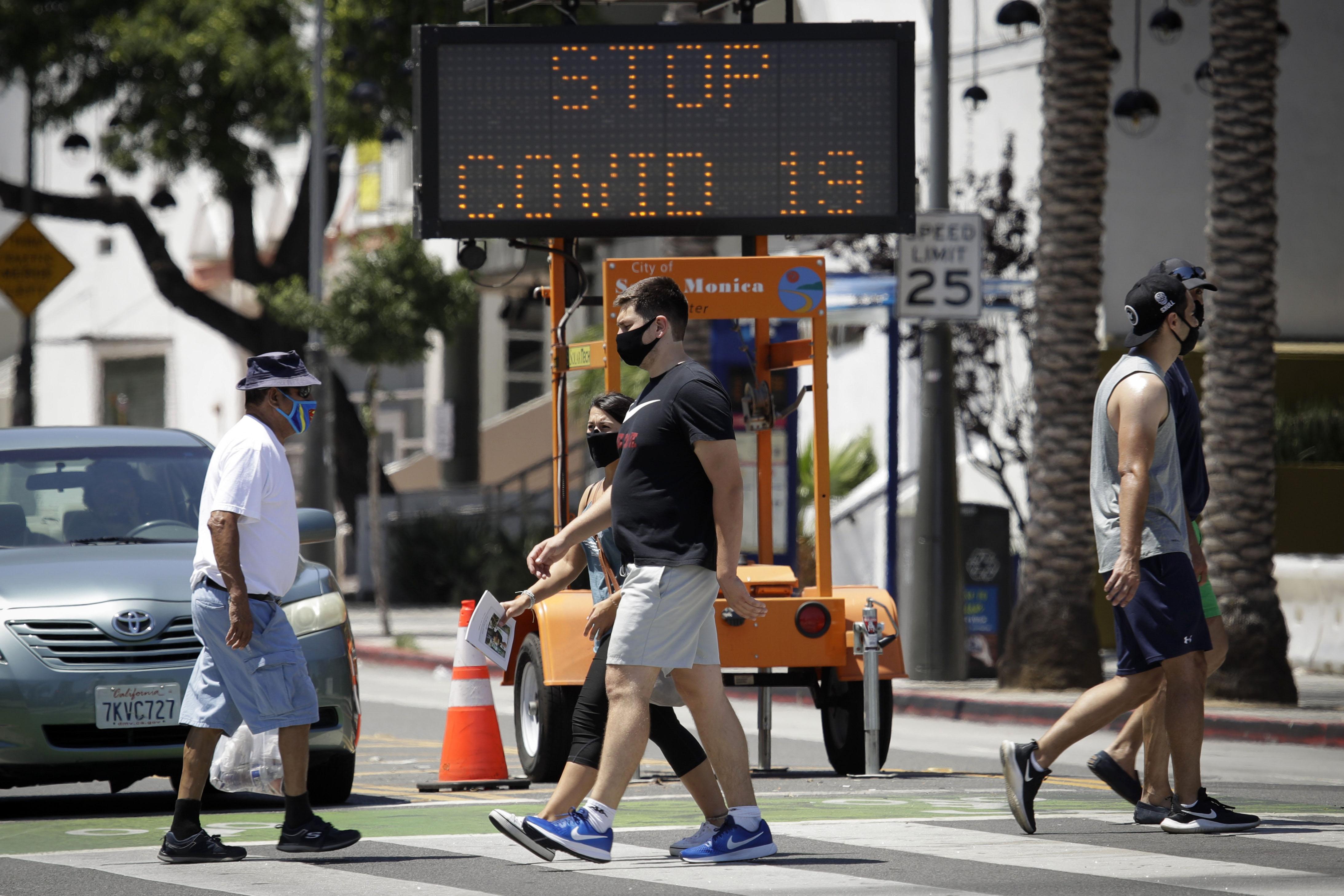 People cross a street in Santa Monica, California, on July 12.
