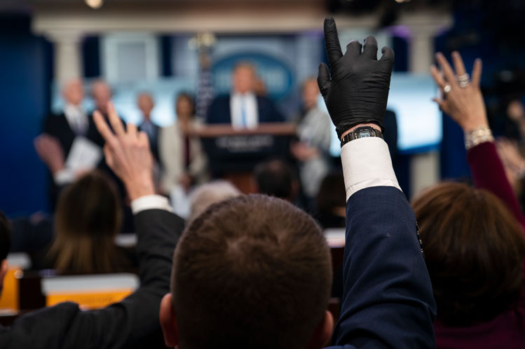 Reporters raise their hands to ask President Donald Trump questions during a news briefing with the coronavirus task force, at the White House, on Monday, March 16, in Washington.