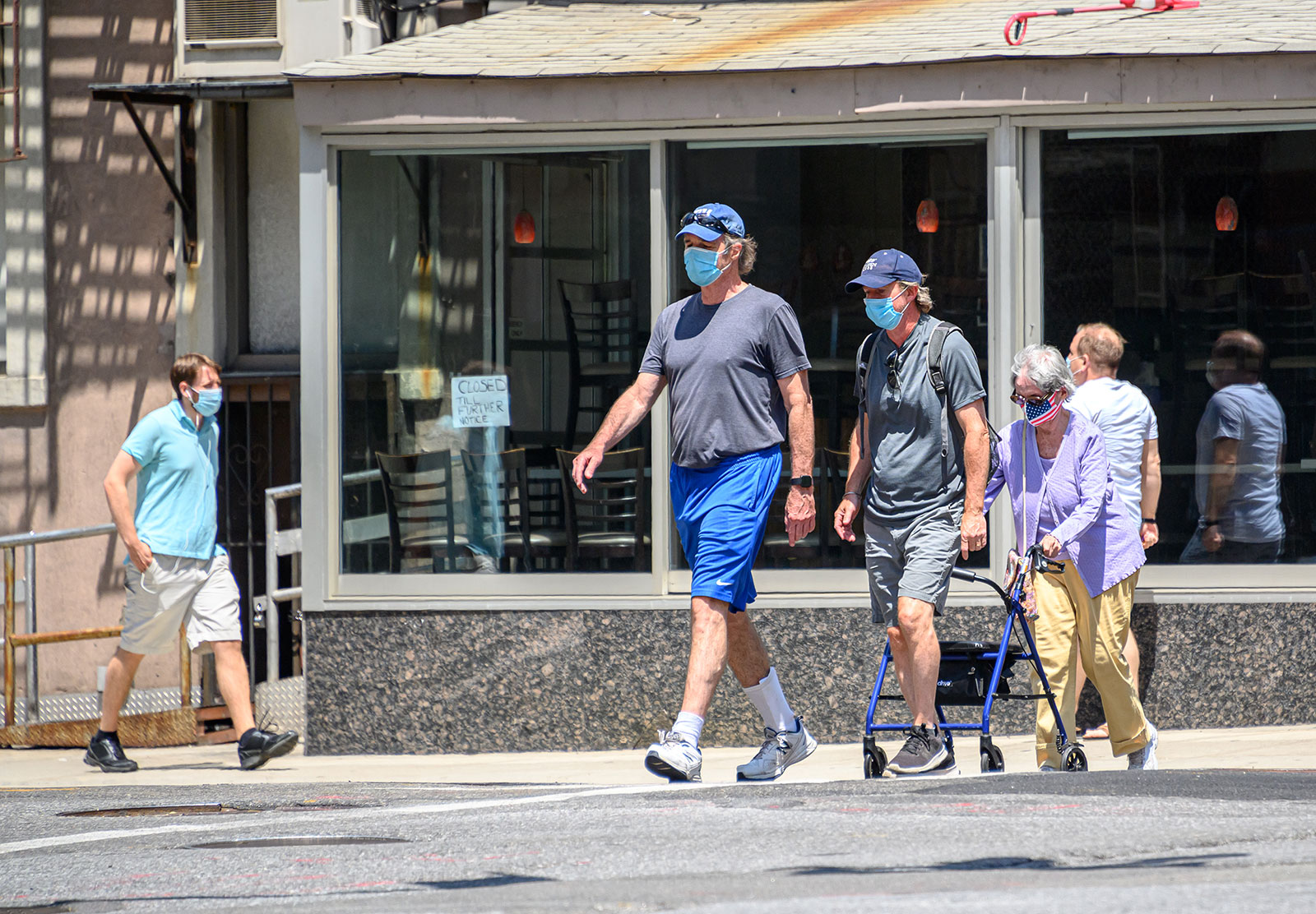 People wear face maskswhile walking in Manhattan on Tuesday, July 28. Dr. Anthony Fauci said on MSNBC Wednesday that universal wearing of masks is one of five principles that could help stop coronavirus surges happening in states.